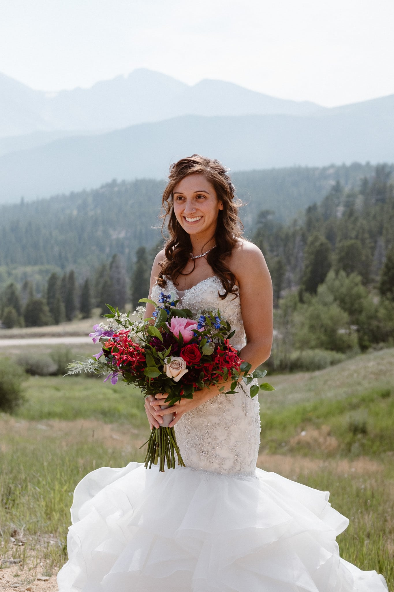 Bride in mermaid wedding dress with large gem colored bouquet.