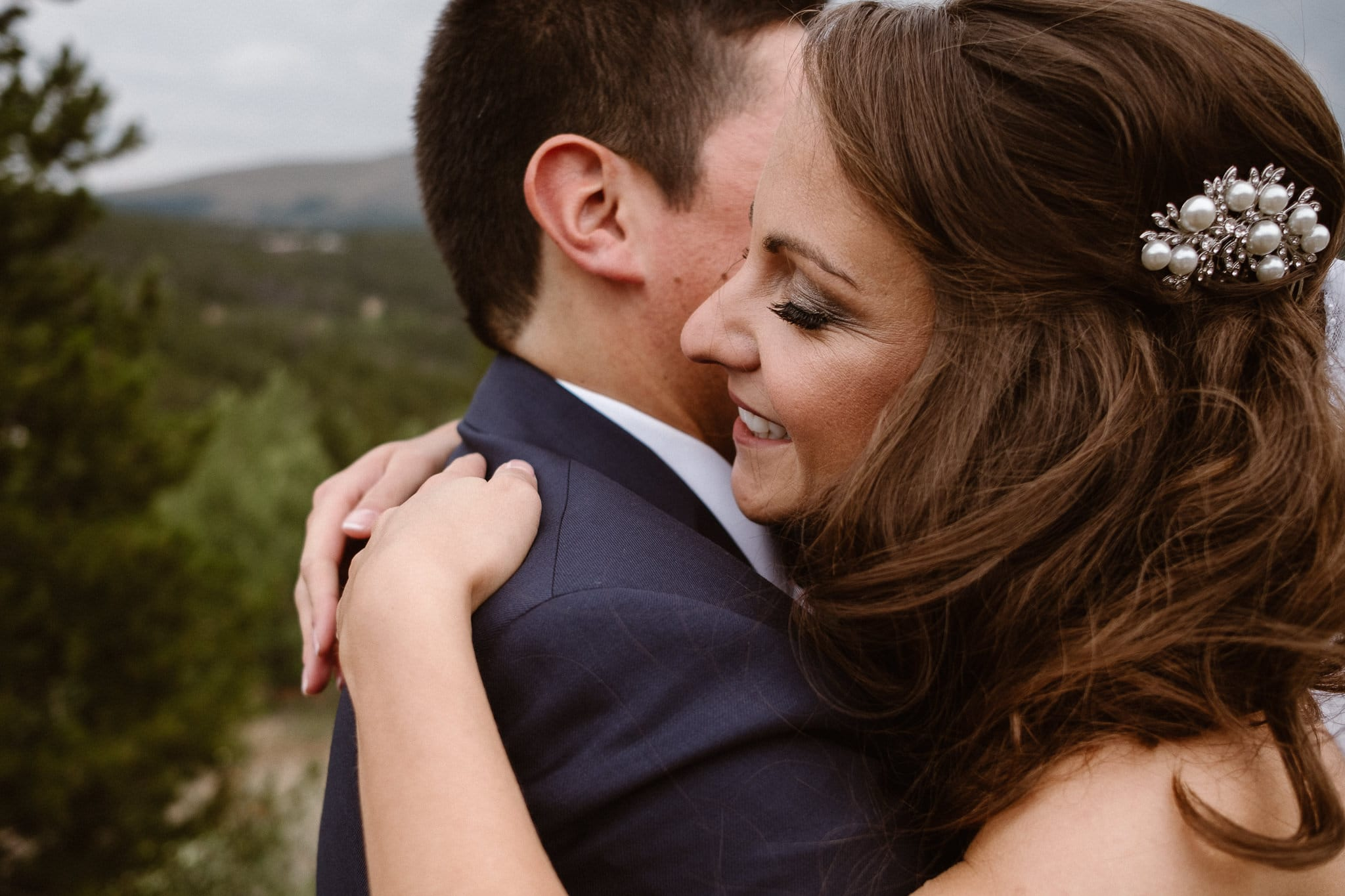 Close up portrait of bride and groom hugging.