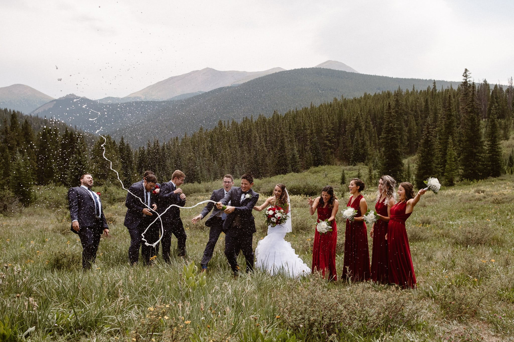 Lodge at Breckenridge Wedding Photographer, Colorado mountain wedding photographer, intimate wedding, bride and groom walking through alpine meadow with wedding party, bride and groom portrait, wedding photos, dark red bridesmaid dresses, popping champagne bottle