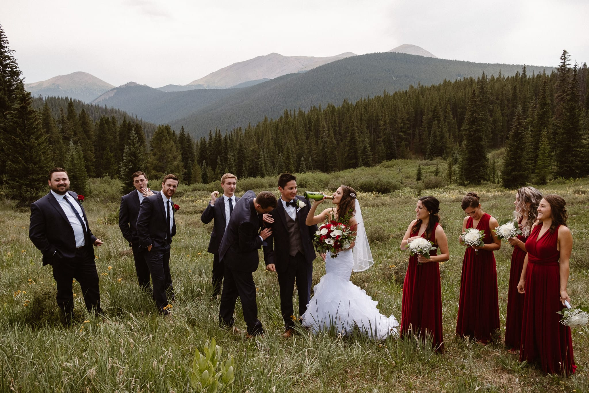 Lodge at Breckenridge Wedding Photographer, Colorado mountain wedding photographer, intimate wedding, bride and groom walking through alpine meadow with wedding party, bride and groom portrait, wedding photos, dark red bridesmaid dresses, bride and groom drinking champagne