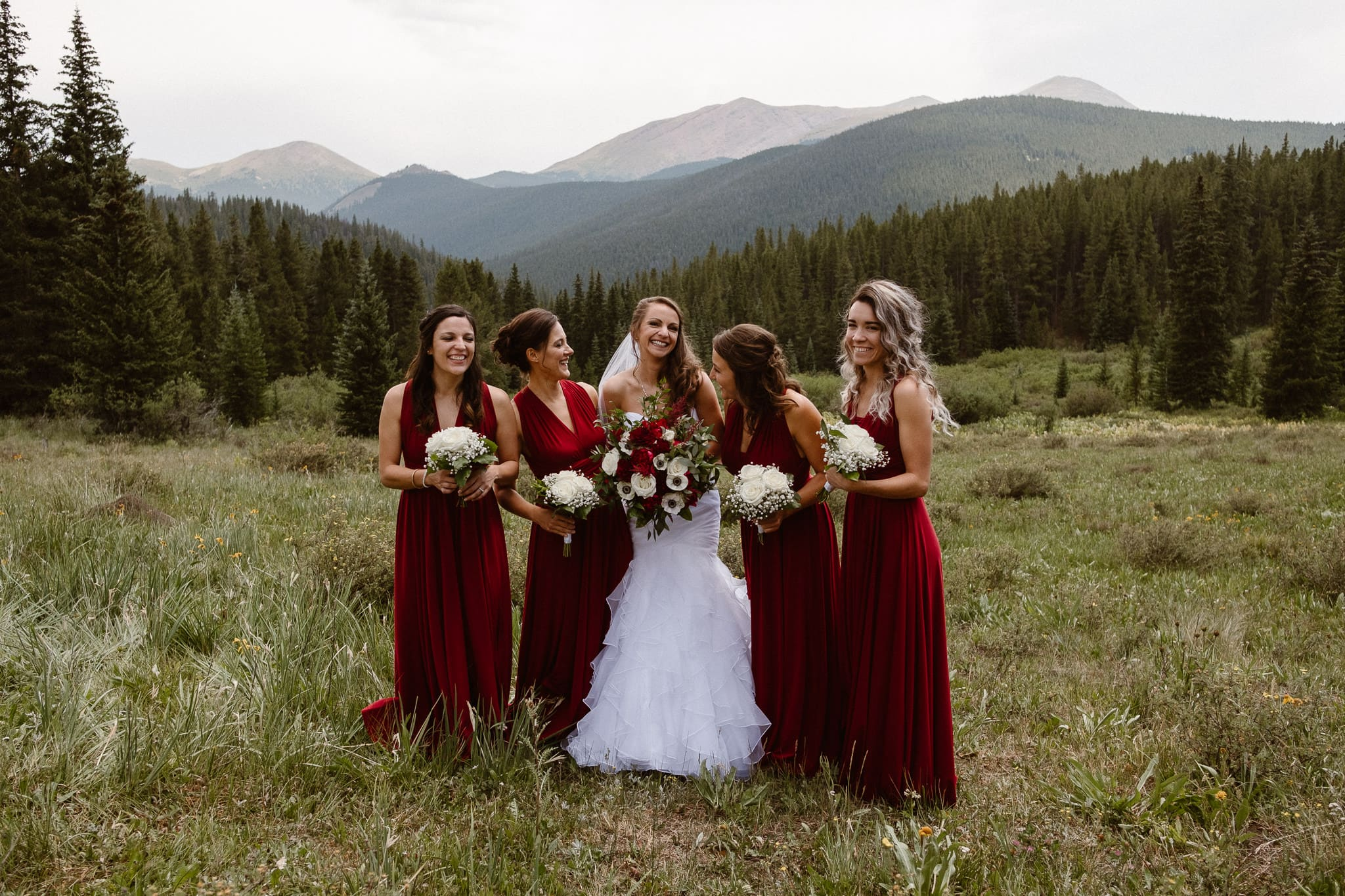 Lodge at Breckenridge Wedding Photographer, Colorado mountain wedding photographer, intimate wedding, bride with bridesmaids, dark red bridesmaid dresses, white and dark red bouquets, mermaid wedding dress