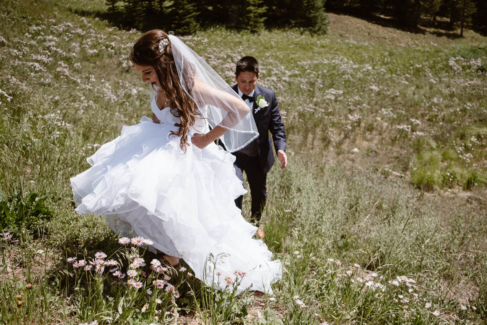 Bride and groom hiking in wildflowers in the mountains at The Lodge at Breckenridge wedding.