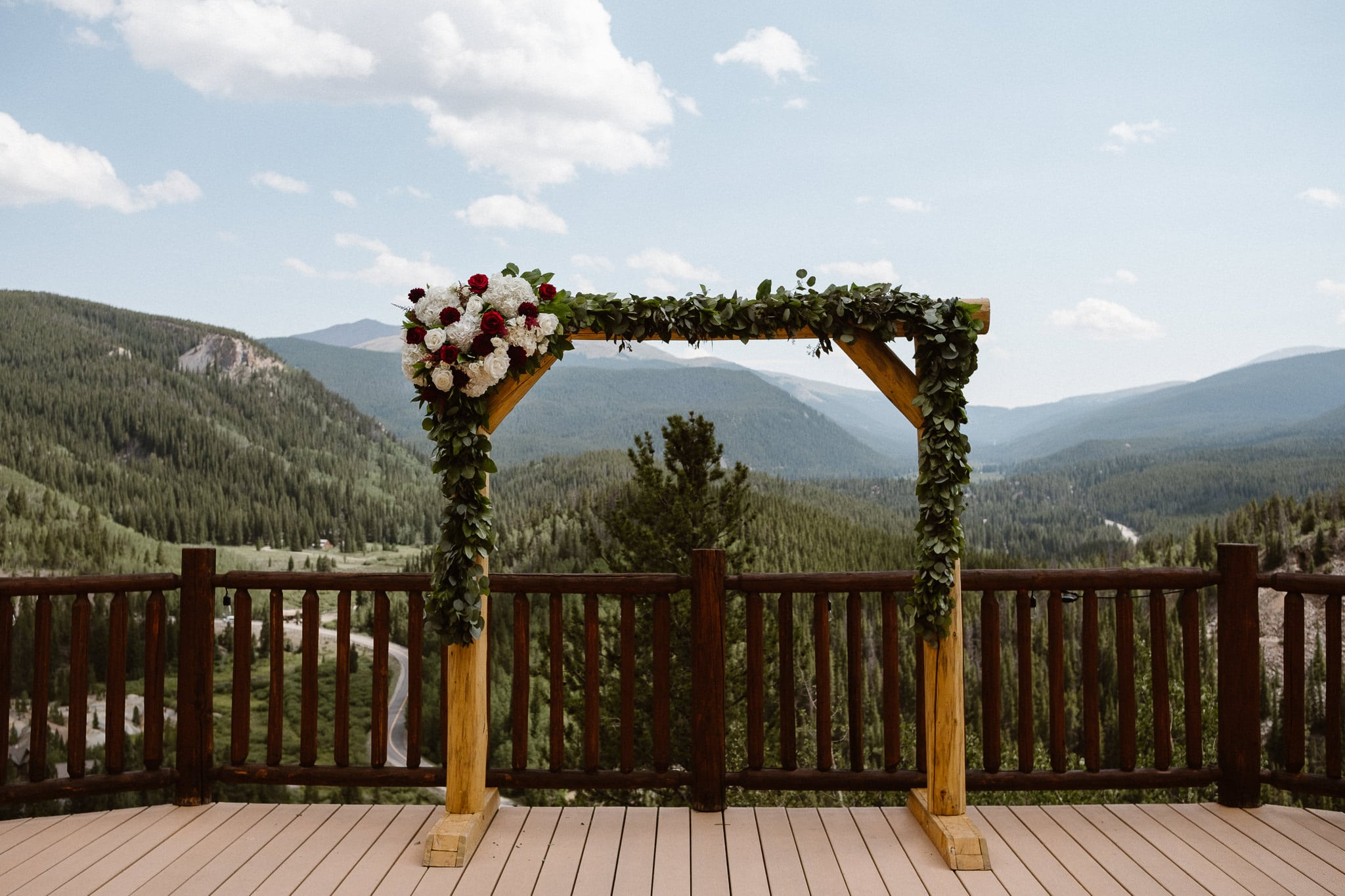 Lodge at Breckenridge Wedding Photographer, Colorado mountain wedding photographer, intimate wedding, wood wedding arch decorated with greenery and white and red roses by Petal & Bean