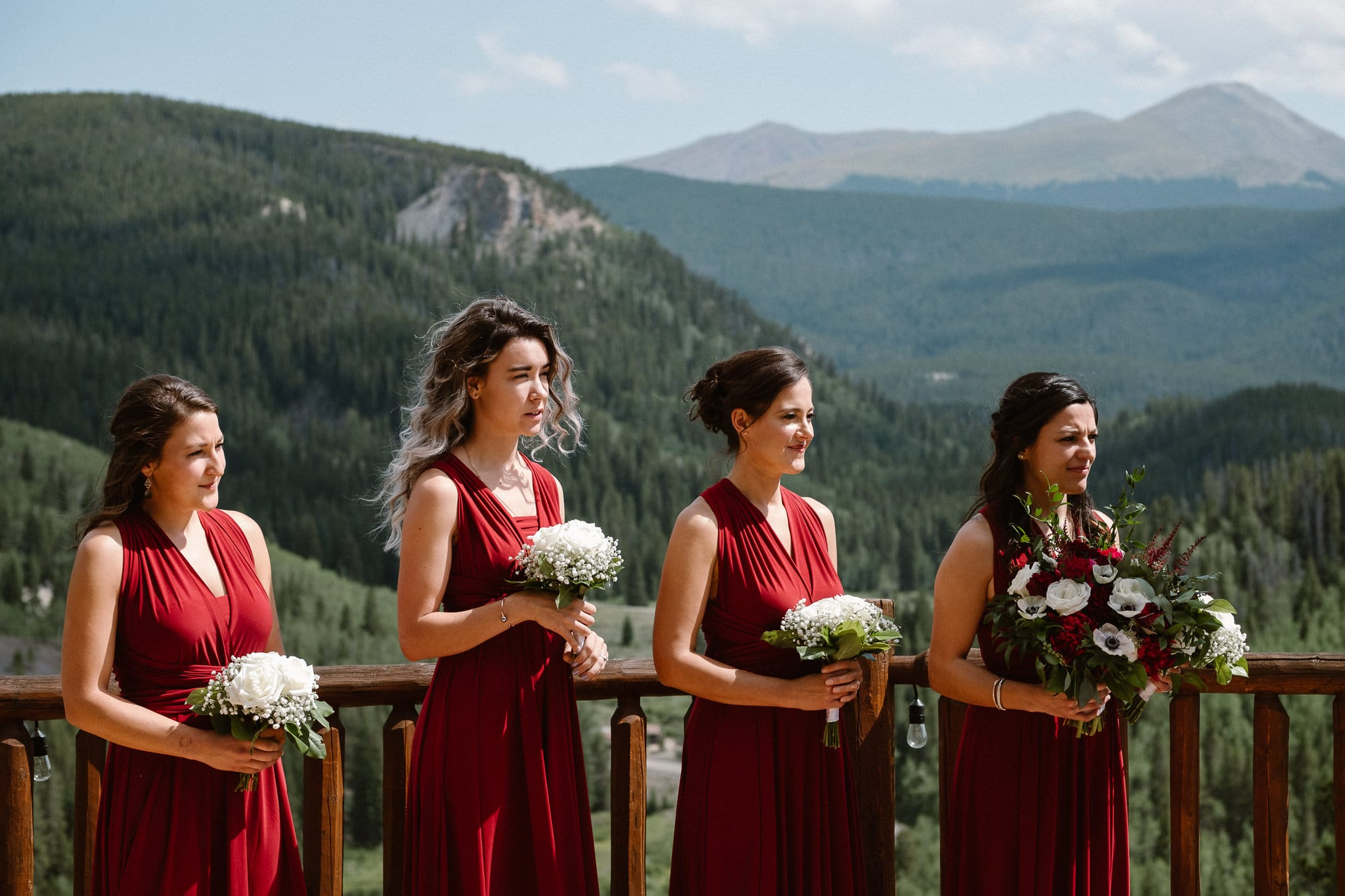 Lodge at Breckenridge Wedding Photographer, Colorado mountain wedding photographer, intimate wedding ceremony, bridesmaids in front of mountains, dark red bridesmaid dresses