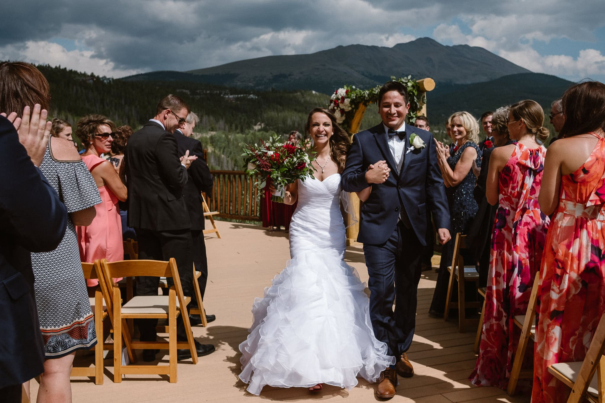Lodge at Breckenridge Wedding Photographer, Colorado mountain wedding photographer, intimate wedding ceremony on deck with mountain views, bride and groom celebrating, recessional