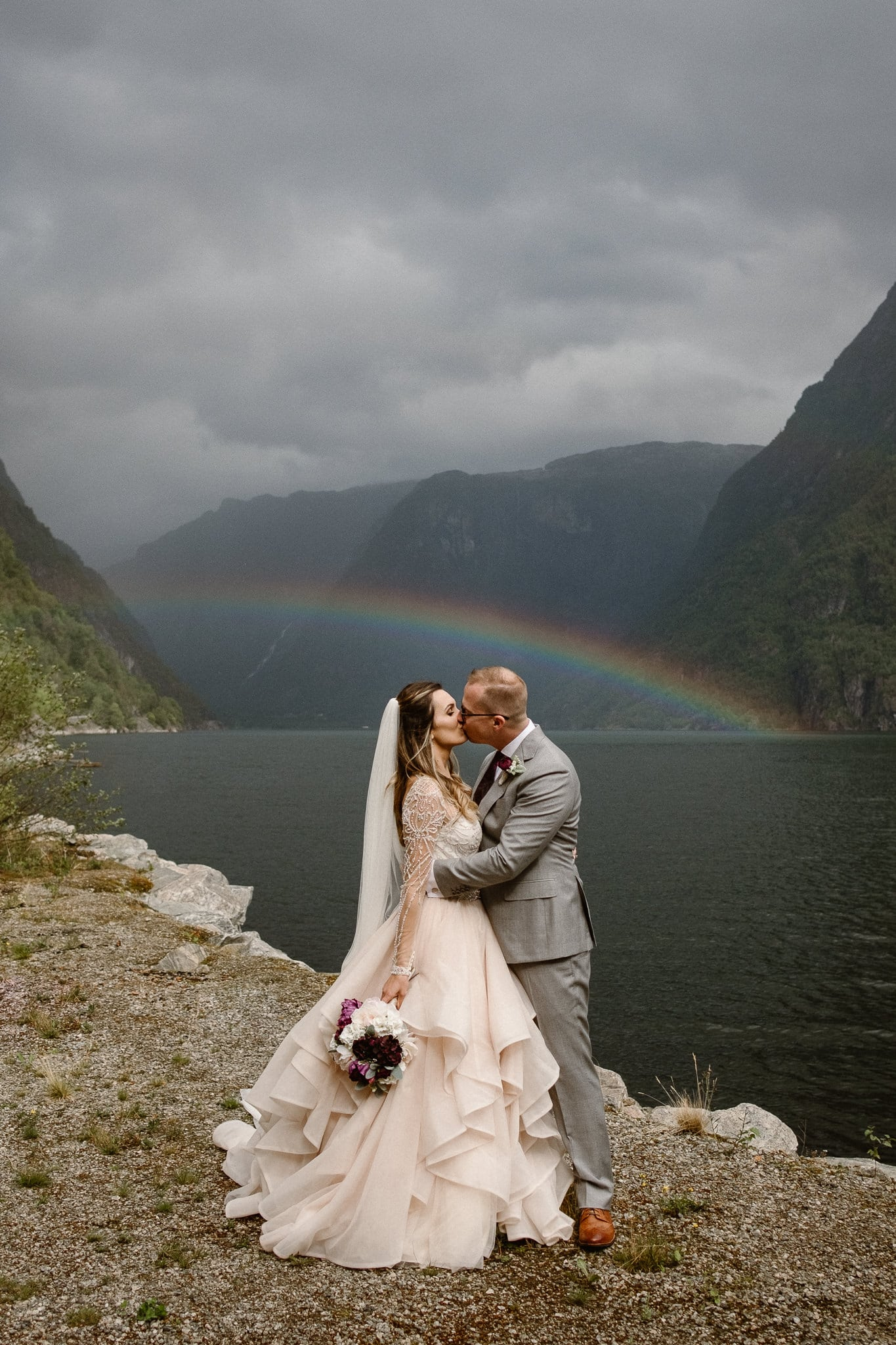 Norway destination wedding photographer, Hardangerfjord bryllup, norsk bryllupsfotograf, Bergen fjord elopement photographer, bride and groom kissing under rainbow in fjord, bryllupsfotograf