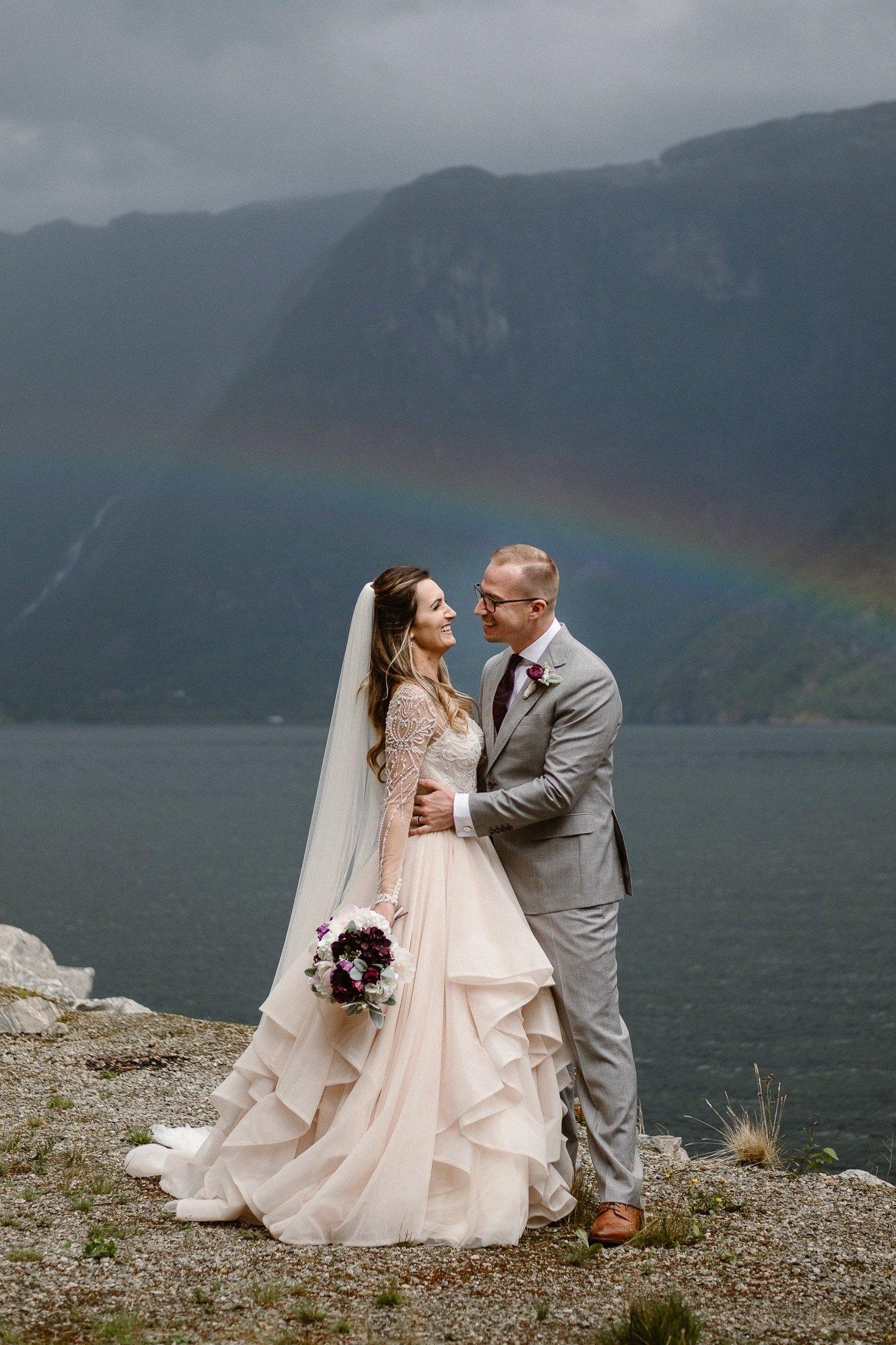Norway destination wedding photographer, Hardangerfjord bryllup, norsk bryllupsfotograf, Bergen fjord elopement photographer, bride and groom kissing under rainbow in fjord,