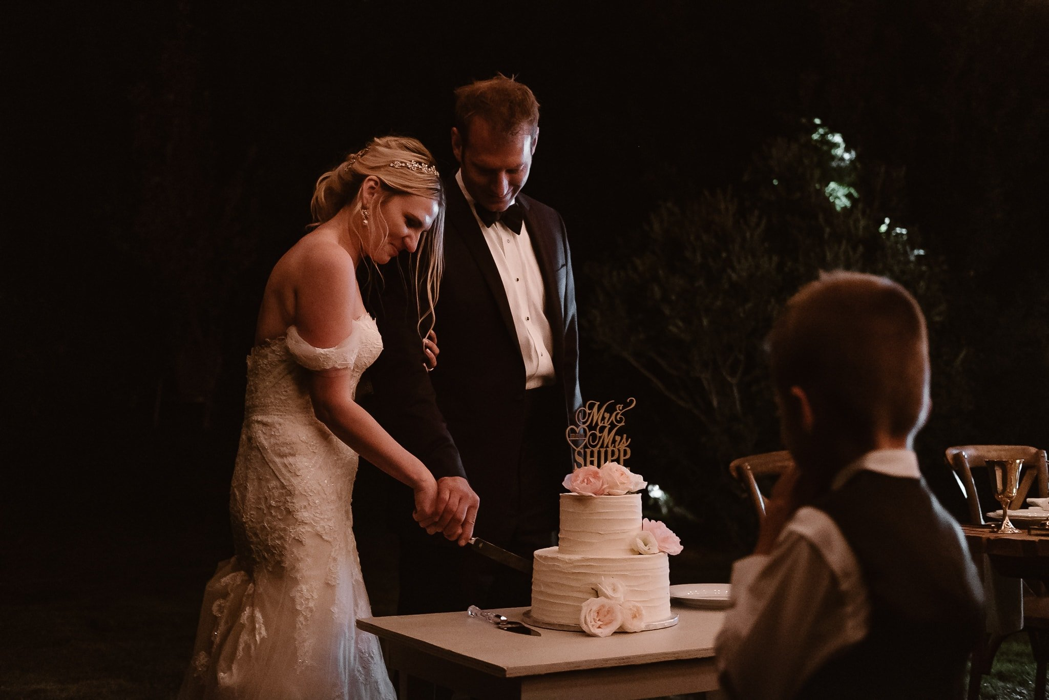 Aspen ranch wedding, Colorado mountain wedding photographer, bride and groom cutting classic white wedding cake with pale pink flowers