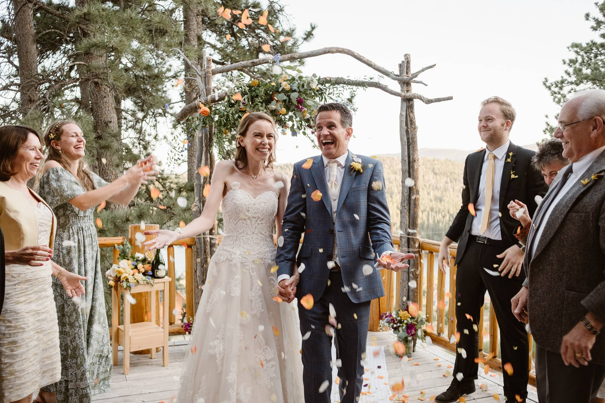 Red Feather Lakes elopement photographer, Colorado intimate cabin wedding, cabin wedding ceremony, bride and groom flower throw processional