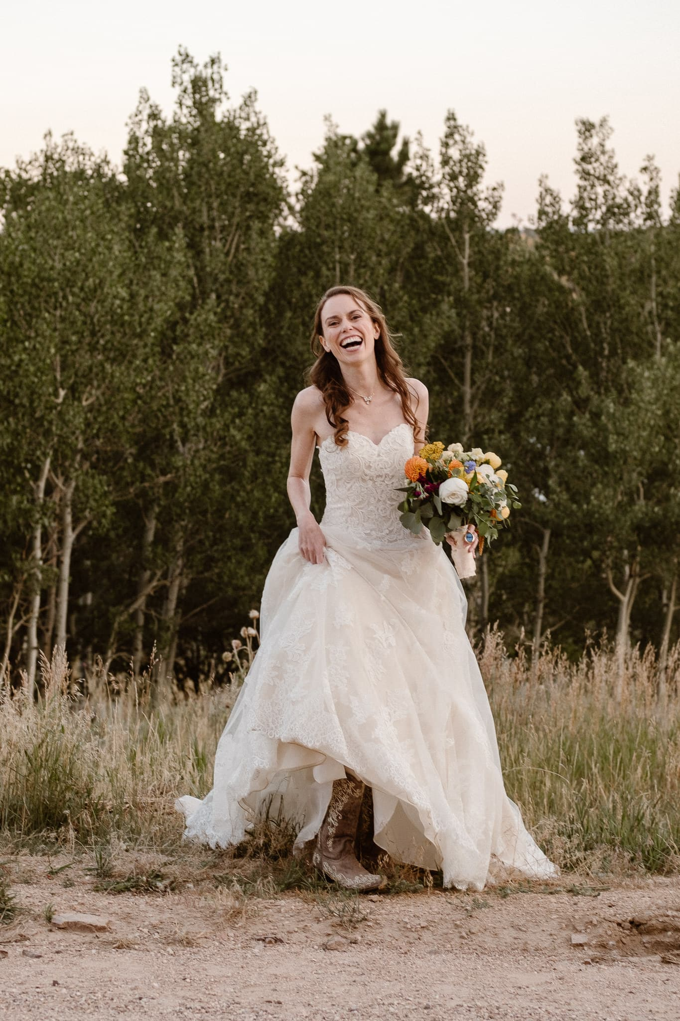 Red Feather Lakes elopement photographer, Colorado intimate cabin wedding, bride portrait with bouquet by Lace & Lilies, bride wearing cowboy boots