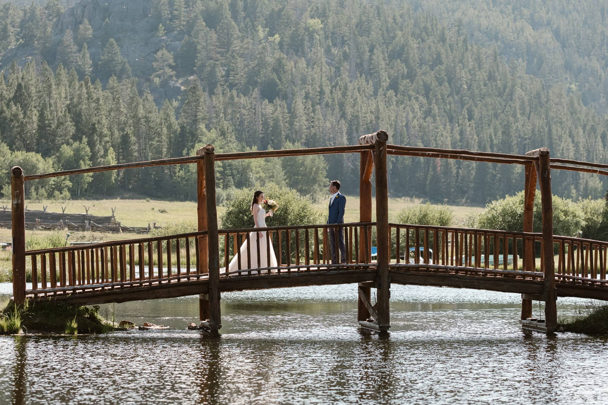 Red Feather Lakes elopement photographer, Colorado intimate cabin wedding, bride and groom first look on bridge