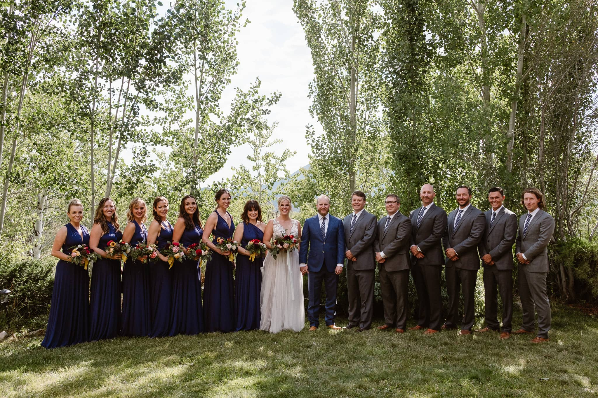 Steamboat Springs wedding photographer, La Joya Dulce wedding, Colorado ranch wedding venues, bride and groom with wedding party, bridesmaids in navy dresses, dark gray groomsmen suits