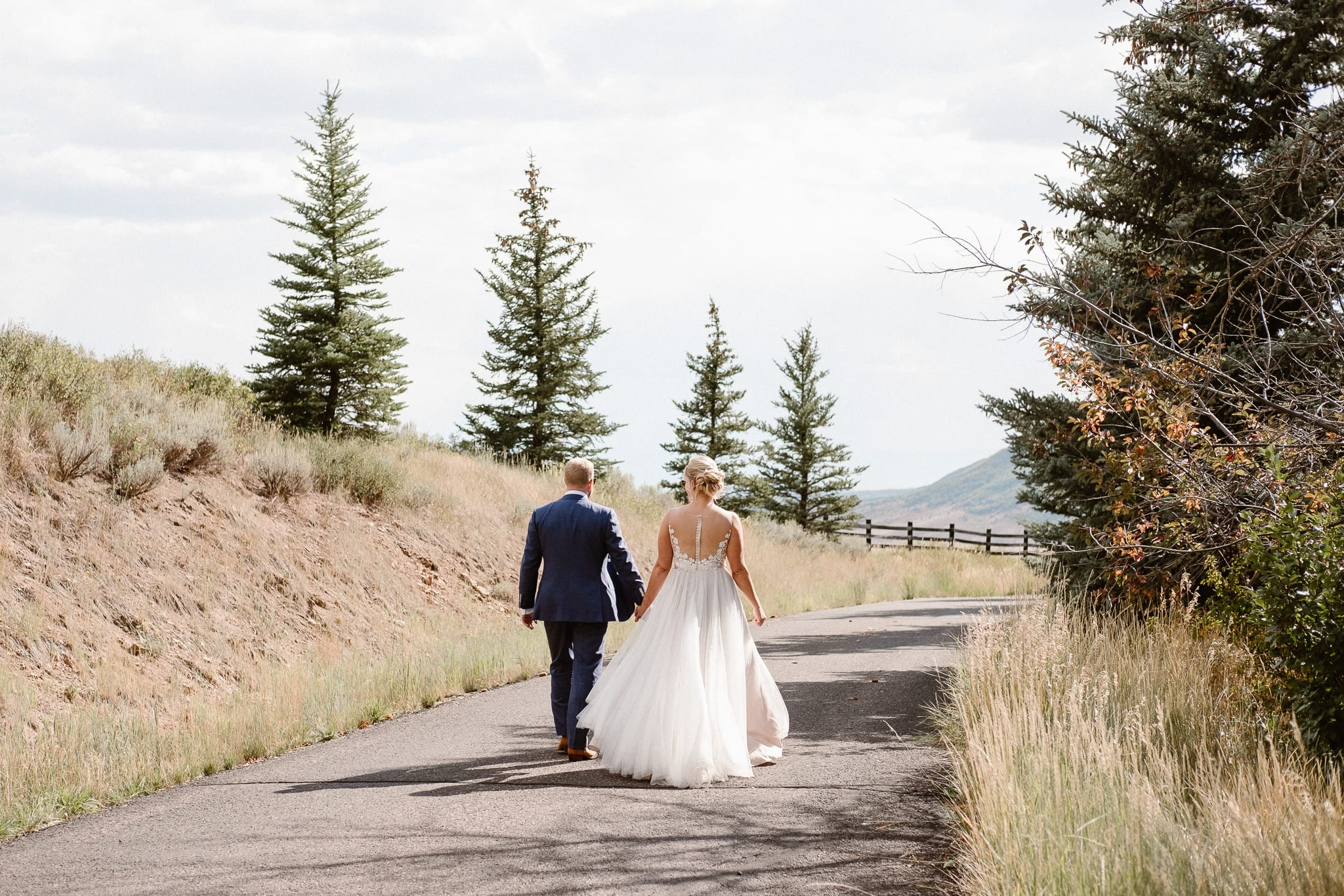 Steamboat Springs wedding photographer, La Joya Dulce wedding, Colorado ranch wedding venues, bride and groom portraits, bride and groom walking down road