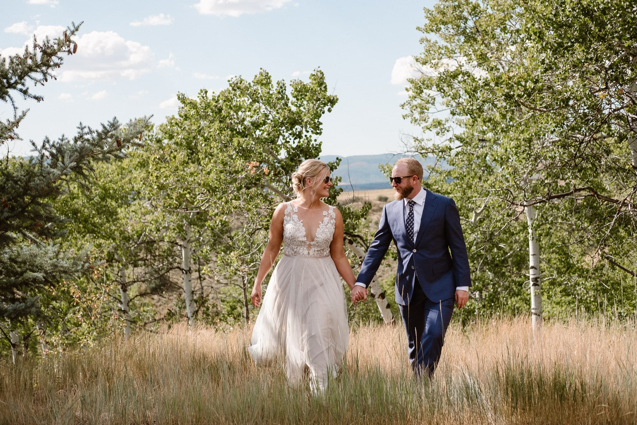 Steamboat Springs wedding photographer, La Joya Dulce wedding, Colorado ranch wedding venues, bride and groom portraits, bride and groom walking in grass