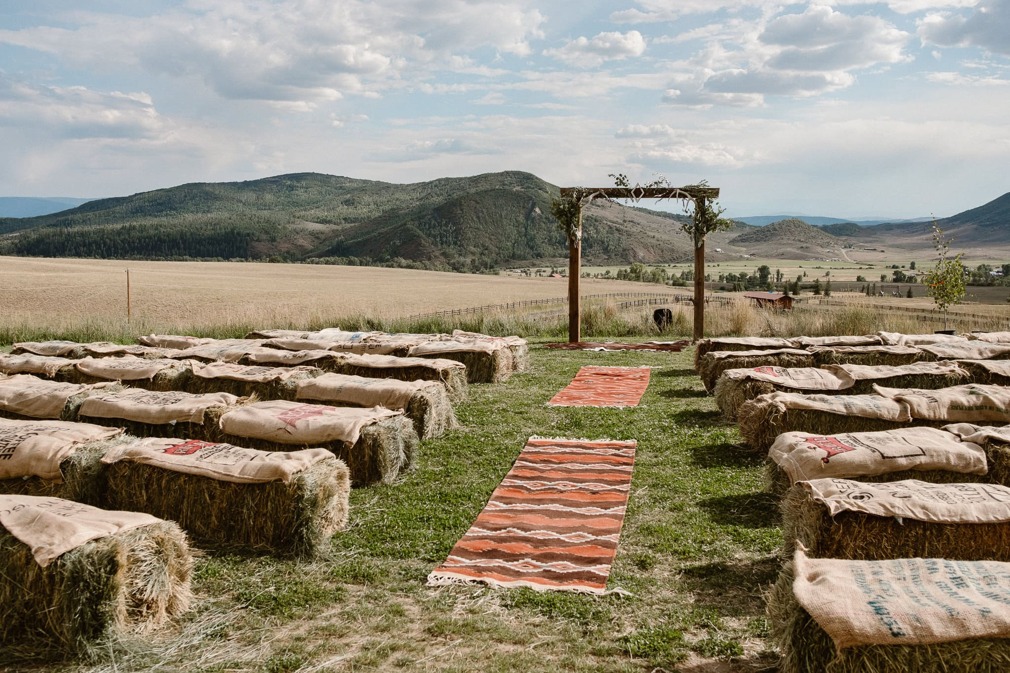 Steamboat Springs wedding photographer, La Joya Dulce wedding, Colorado ranch wedding venues, ceremony site with mountain views, wedding ceremony with hay bales, ceremony aisle with rugs