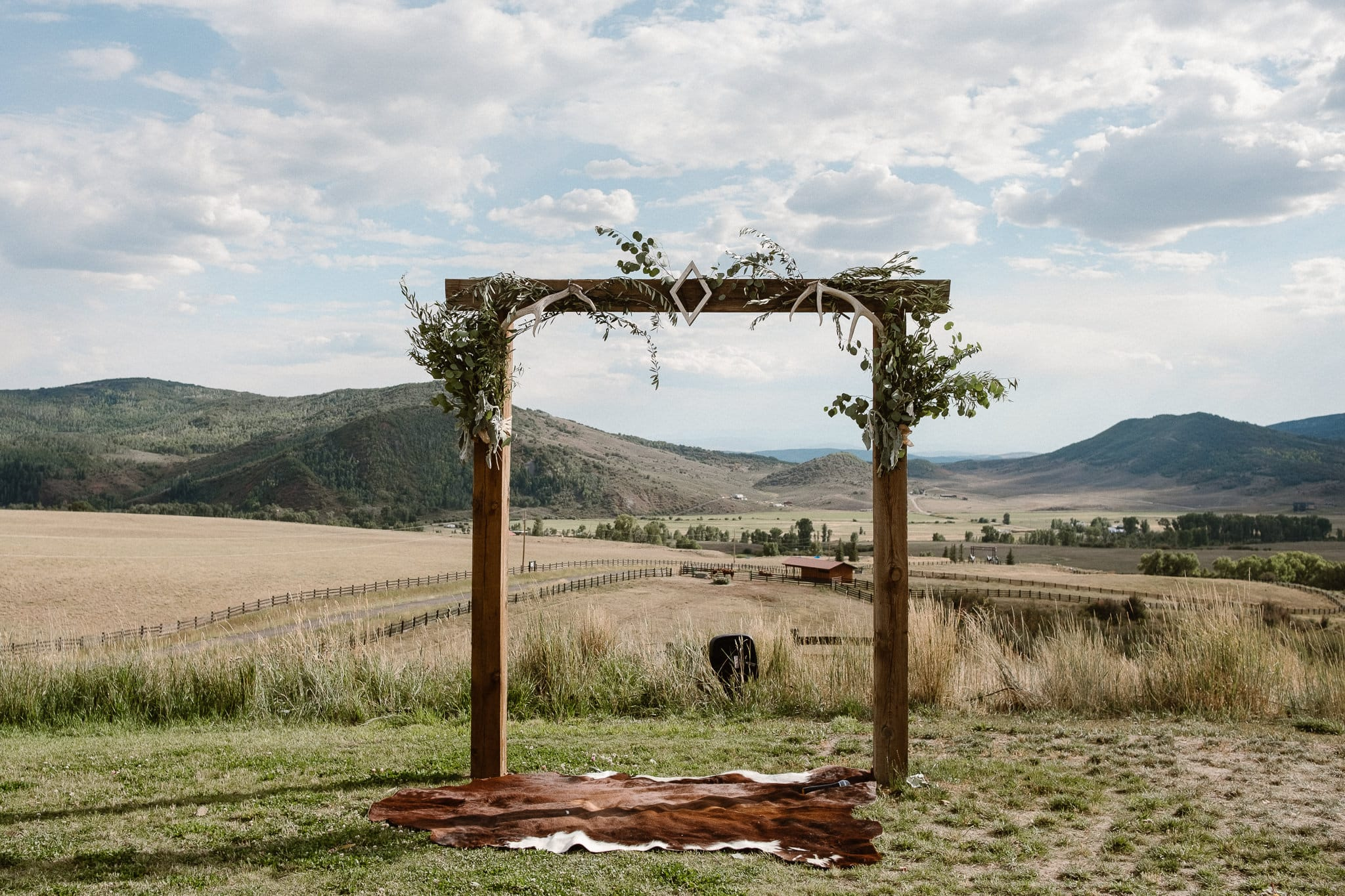 Steamboat Springs wedding photographer, La Joya Dulce wedding, Colorado ranch wedding venues, ceremony site with mountain views, wedding ceremony with hay bales, ceremony aisle with rugs, cowhide rug
