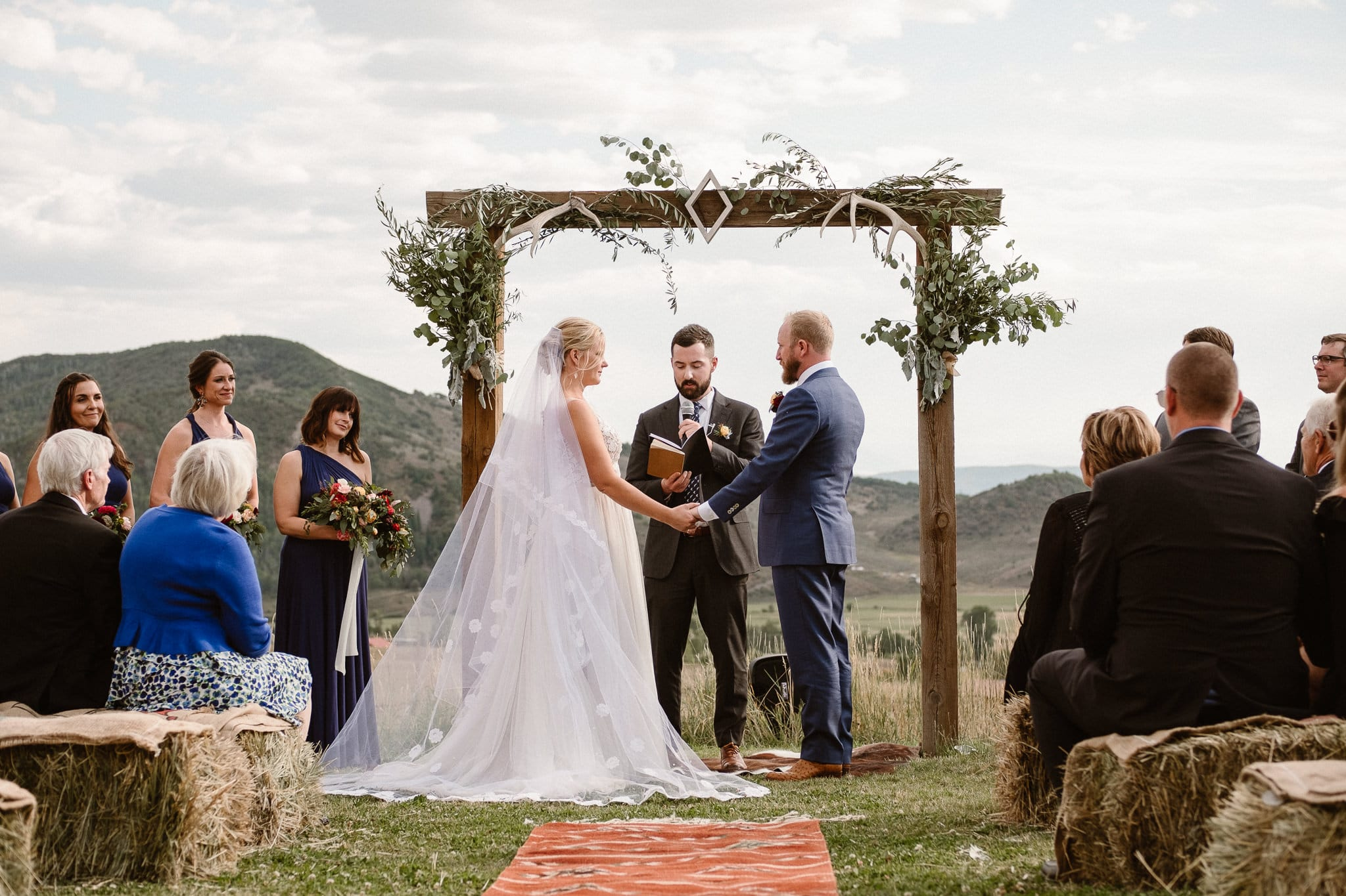 Steamboat Springs wedding photographer, La Joya Dulce wedding, Colorado ranch wedding venues, outdoor wedding ceremony, bridesmaids watching wedding ceremony, bride and groom holding hands