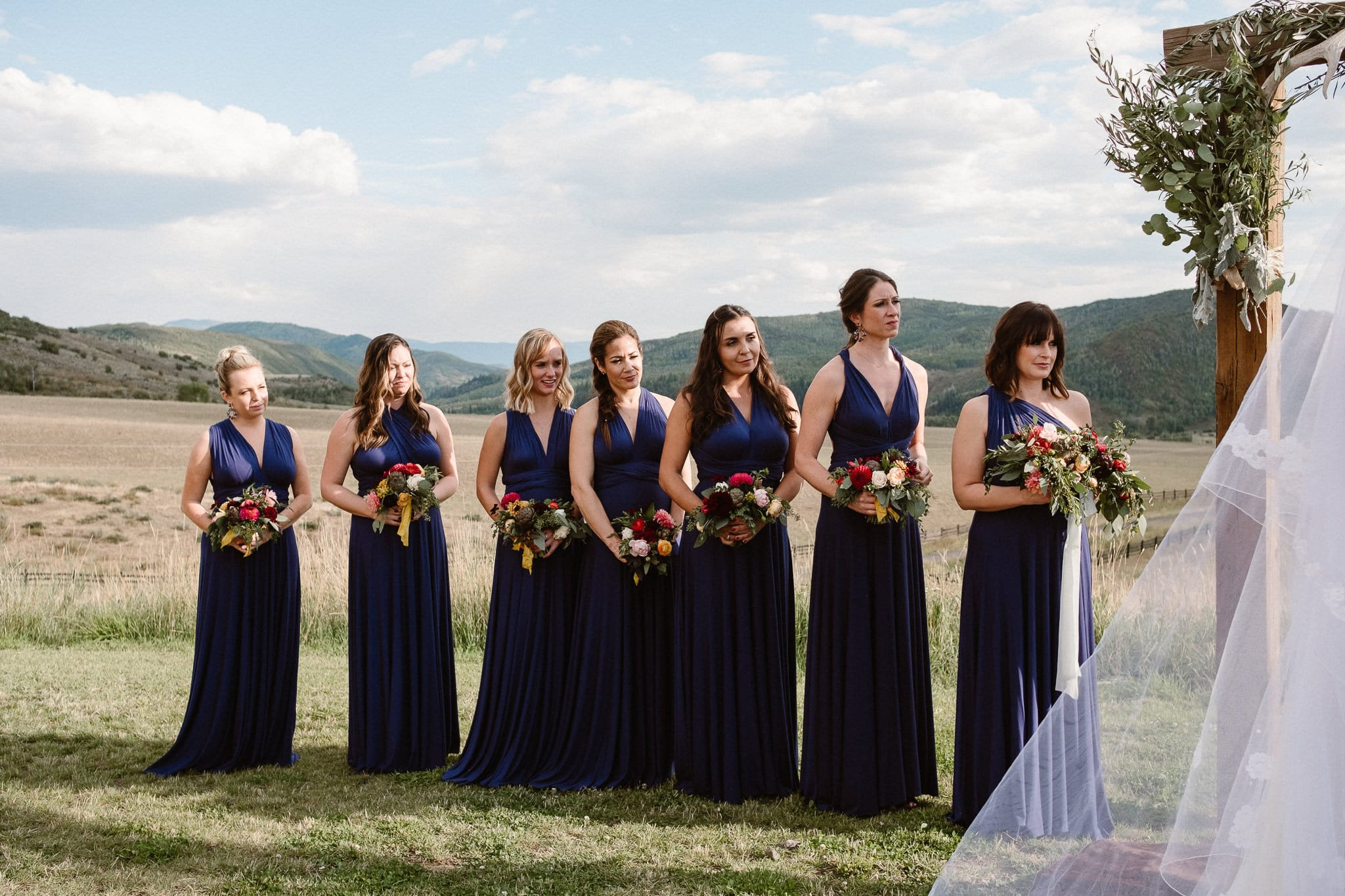 Steamboat Springs wedding photographer, La Joya Dulce wedding, Colorado ranch wedding venues, outdoor wedding ceremony, bridesmaids watching wedding ceremony, bridesmaids in dark blue navy multi way dresses