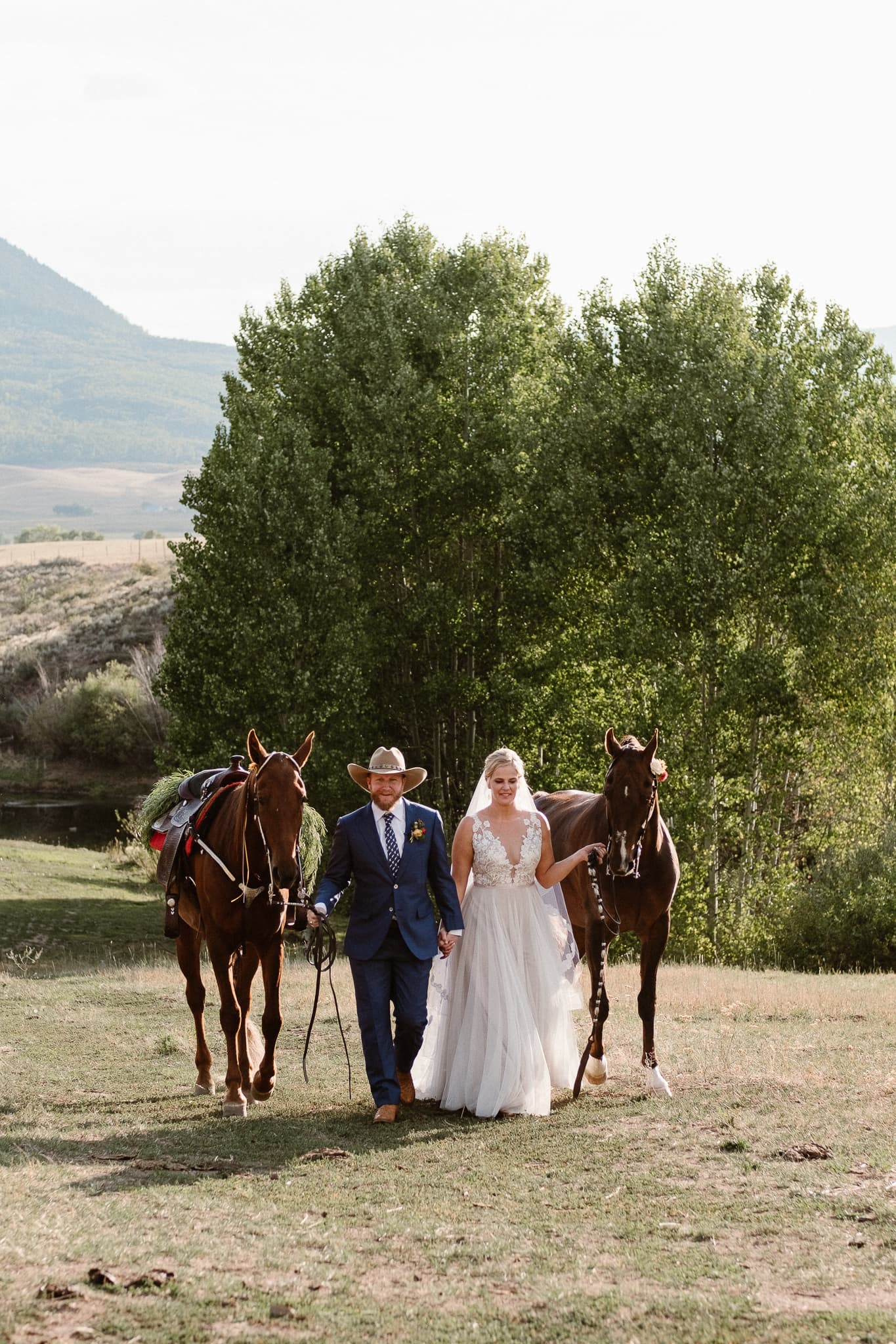 Steamboat Springs wedding photographer, La Joya Dulce wedding, Colorado ranch wedding venues, outdoor wedding ceremony, Colorado wedding, Rocky Mountain wedding, ranch wedding, bride and groom walking with horses