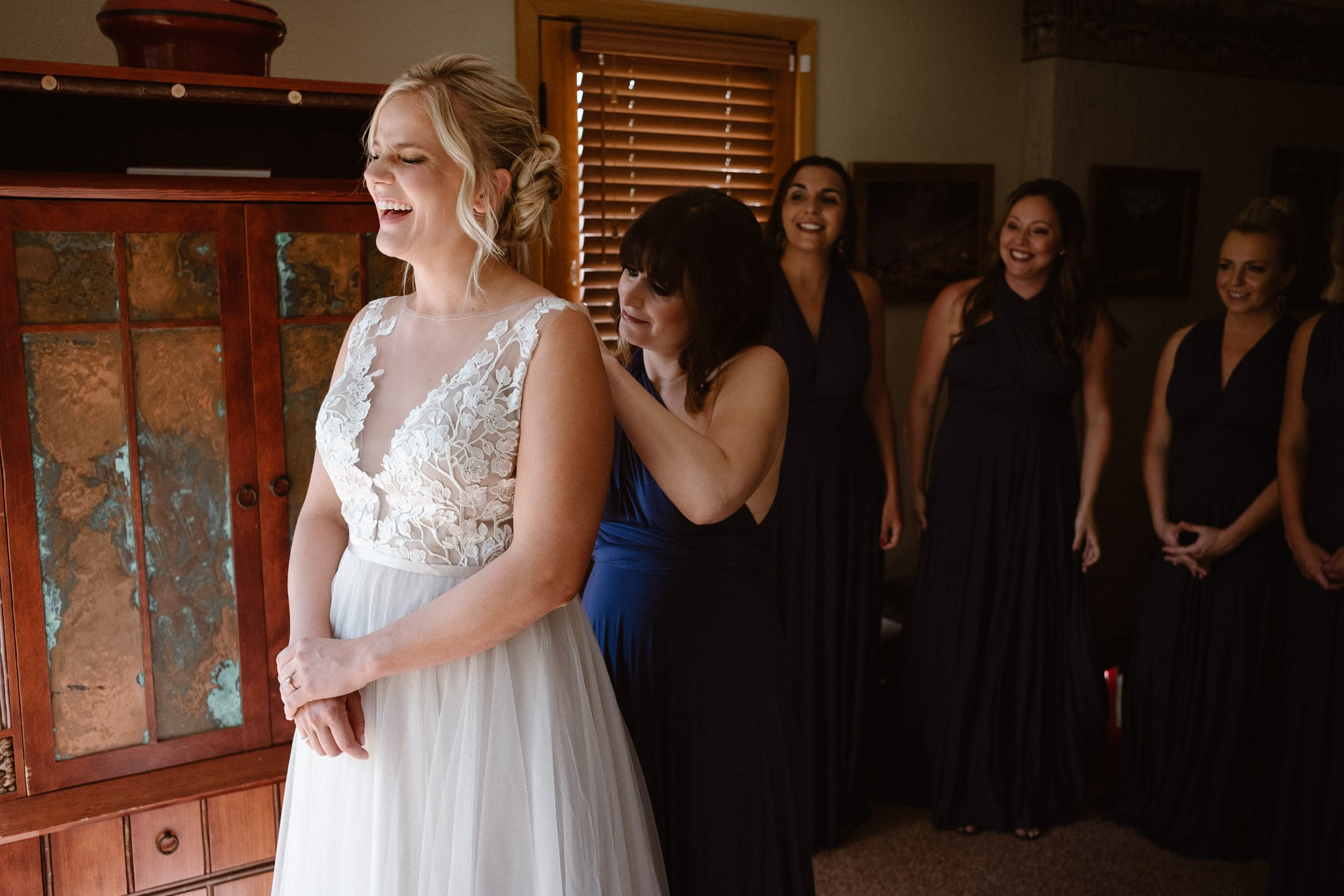 Steamboat Springs wedding photographer, La Joya Dulce wedding, Colorado ranch wedding venues, bride putting on wedding dress, bridesmaids helping bride, getting ready photos