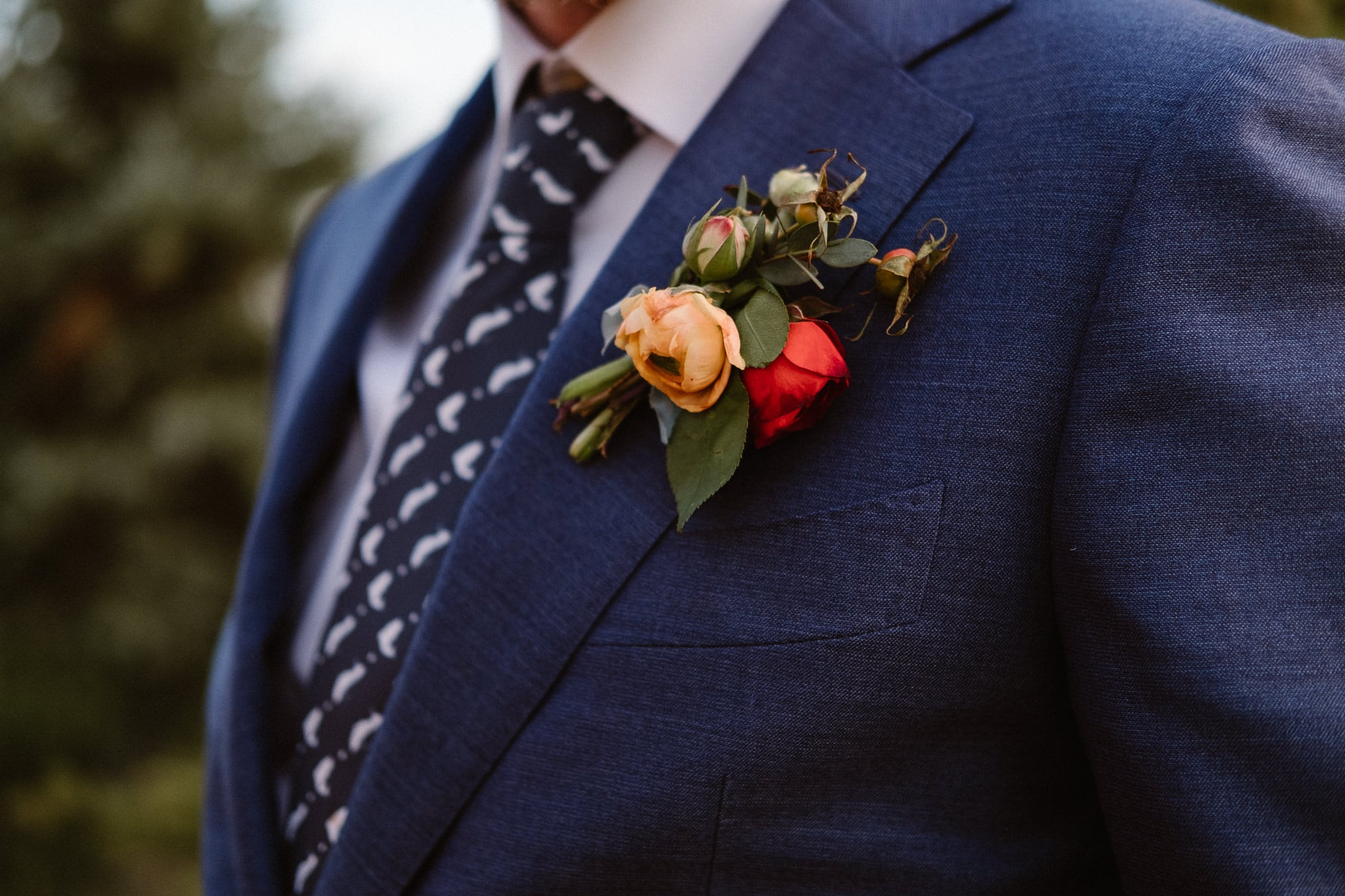 Steamboat Springs wedding photographer, La Joya Dulce wedding, Colorado ranch wedding venues, groom portrait, groom in dark blue dress, groom with fish tie, boutonniere with yellow and red flower