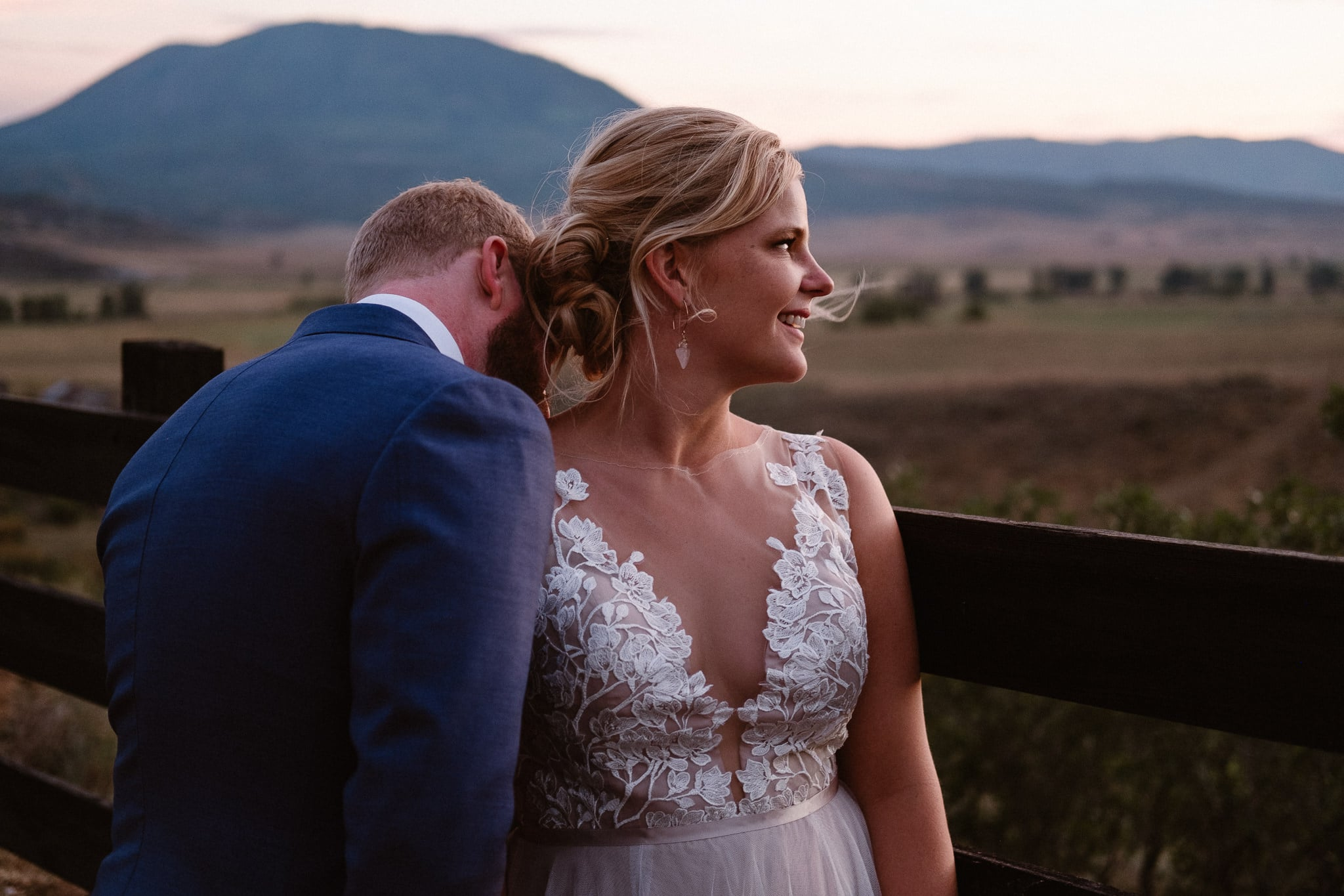 Steamboat Springs wedding photographer, La Joya Dulce wedding, Colorado ranch wedding venues, bridal portraits at sunset, bride with lace top wedding dress, groom kissing bride's neck