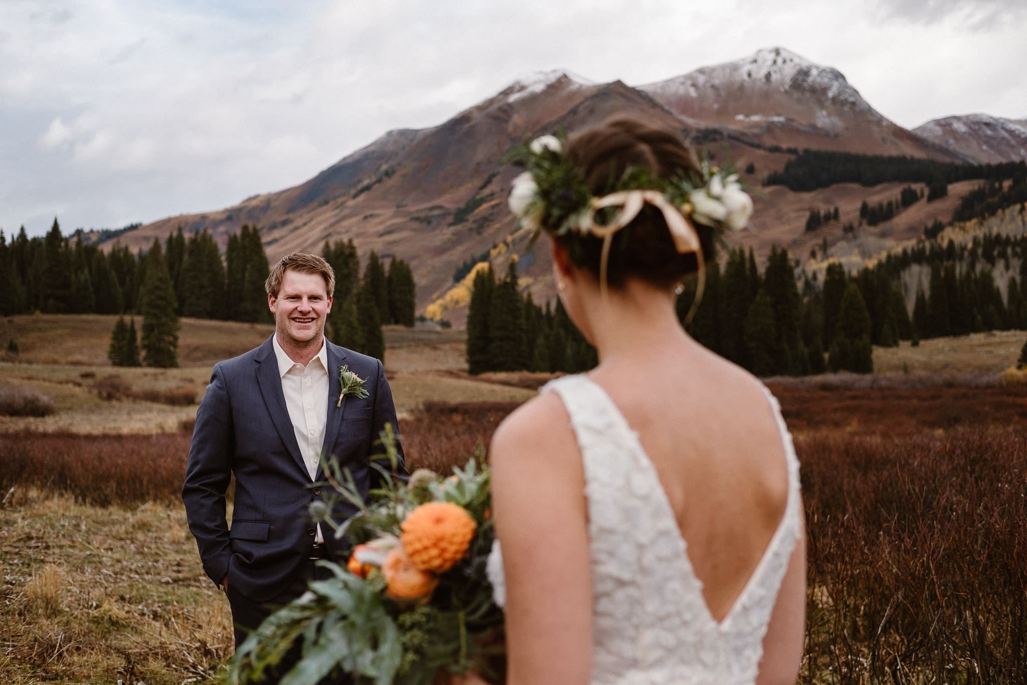 Crested Butte Wedding Photographer, Scarp Ridge Lodge intimate elopement, self solemnized elopement in Colorado, bride and groom portraits, Colorado mountain adventure wedding, bride wearing floral crown, fall color bouquet with orange flowers by From the Ground Up, wedding bouquet, groom looking at bride