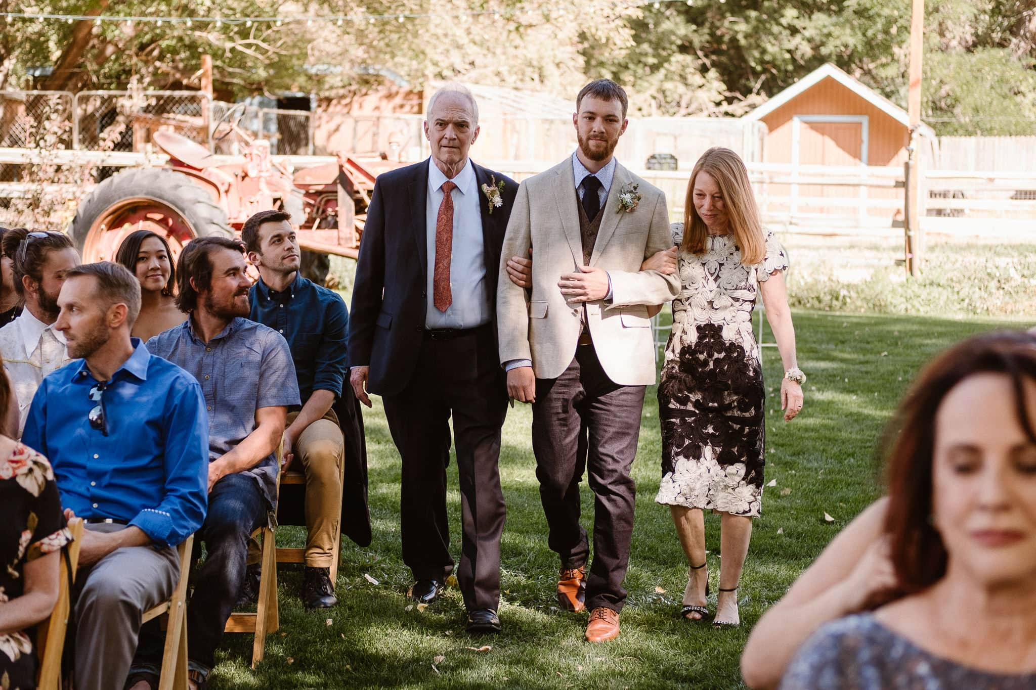 Lyons Farmette wedding photographer, Colorado intimate wedding photographer, wedding ceremony, groom walking down aisle with parents