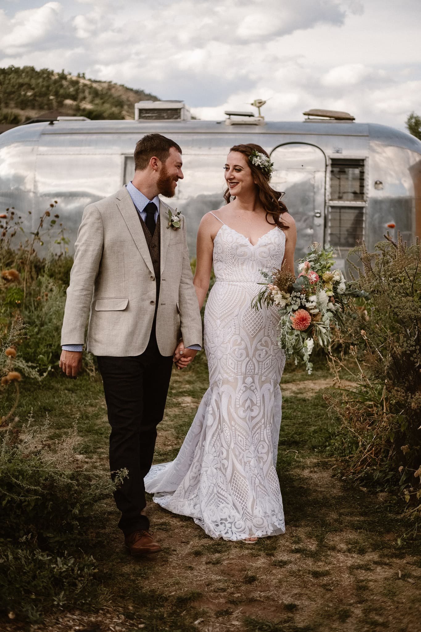 Lyons Farmette wedding photographer, Colorado intimate wedding photographer, bride and groom photos walking by airstream