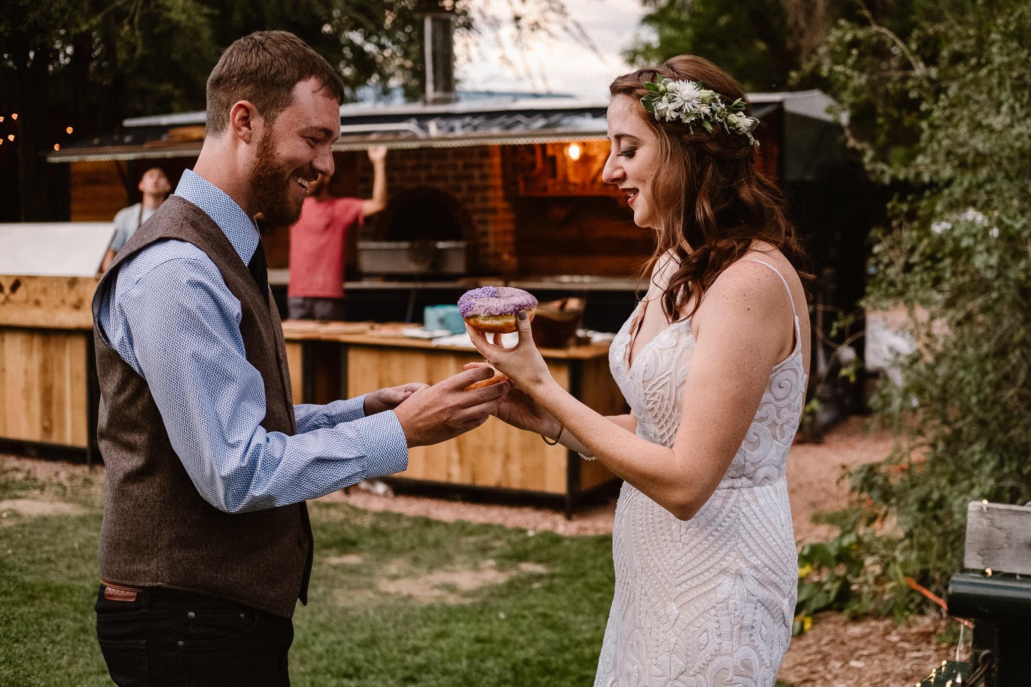 Lyons Farmette wedding photographer, Colorado intimate wedding photographer, wedding donuts by Voodoo Doughnut, bride and groom sharing donut