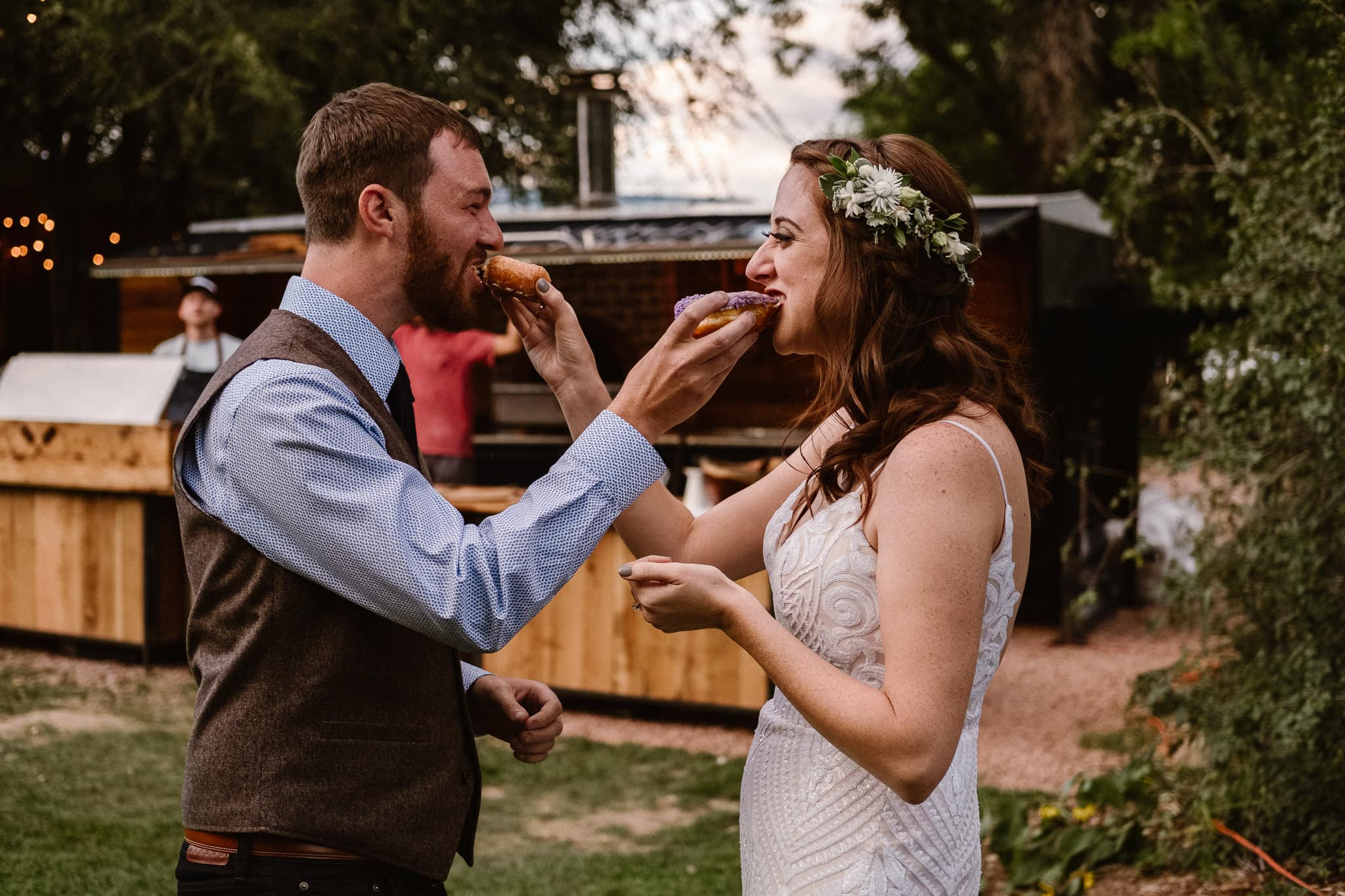Lyons Farmette wedding photographer, Colorado intimate wedding photographer, wedding donuts by Voodoo Doughnut, bride and groom sharing donut