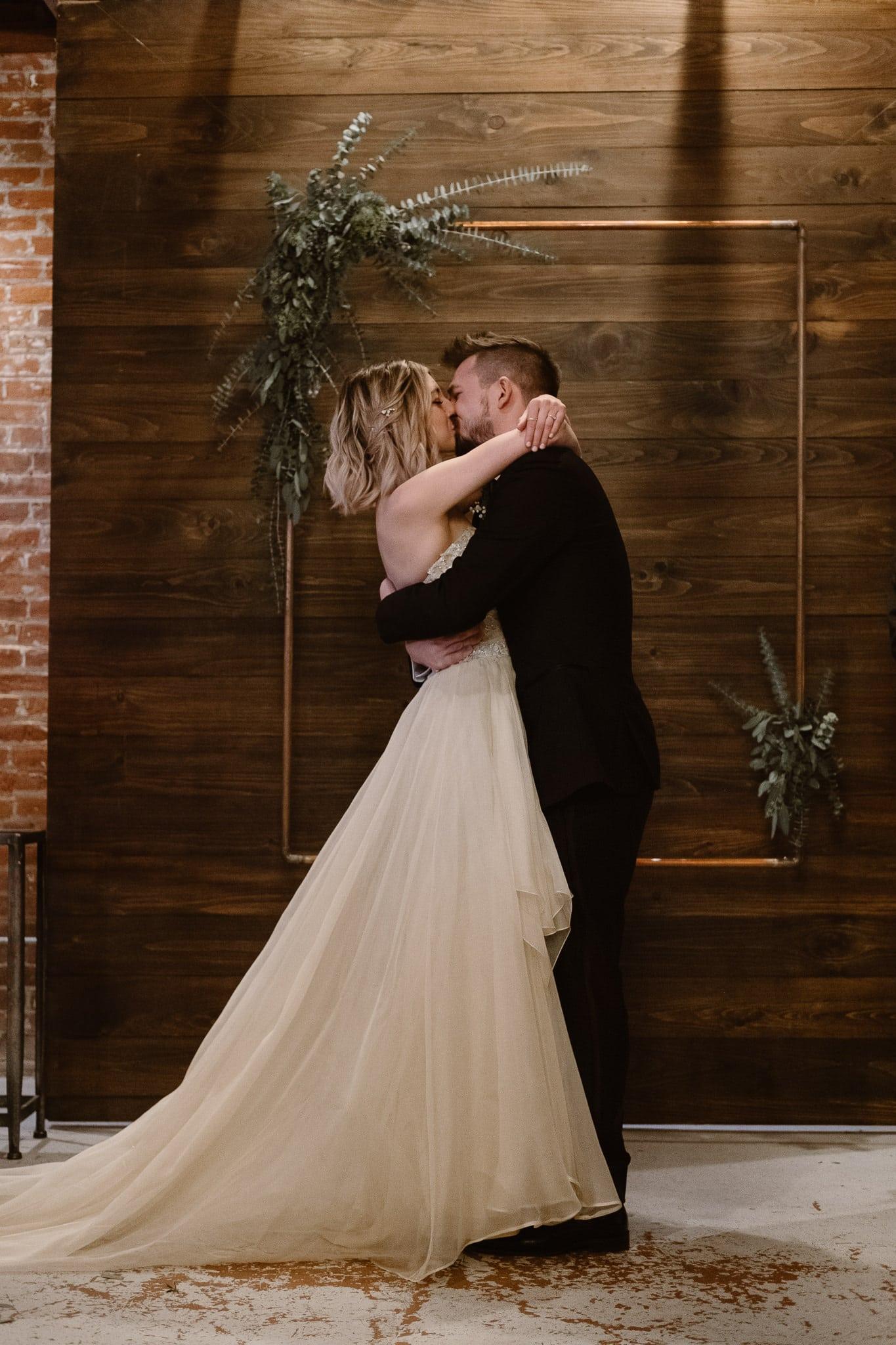 St Vrain Wedding Photographer | Longmont Wedding Photographer | Colorado Winter Wedding Photographer, Colorado industrial chic wedding ceremony, first kiss