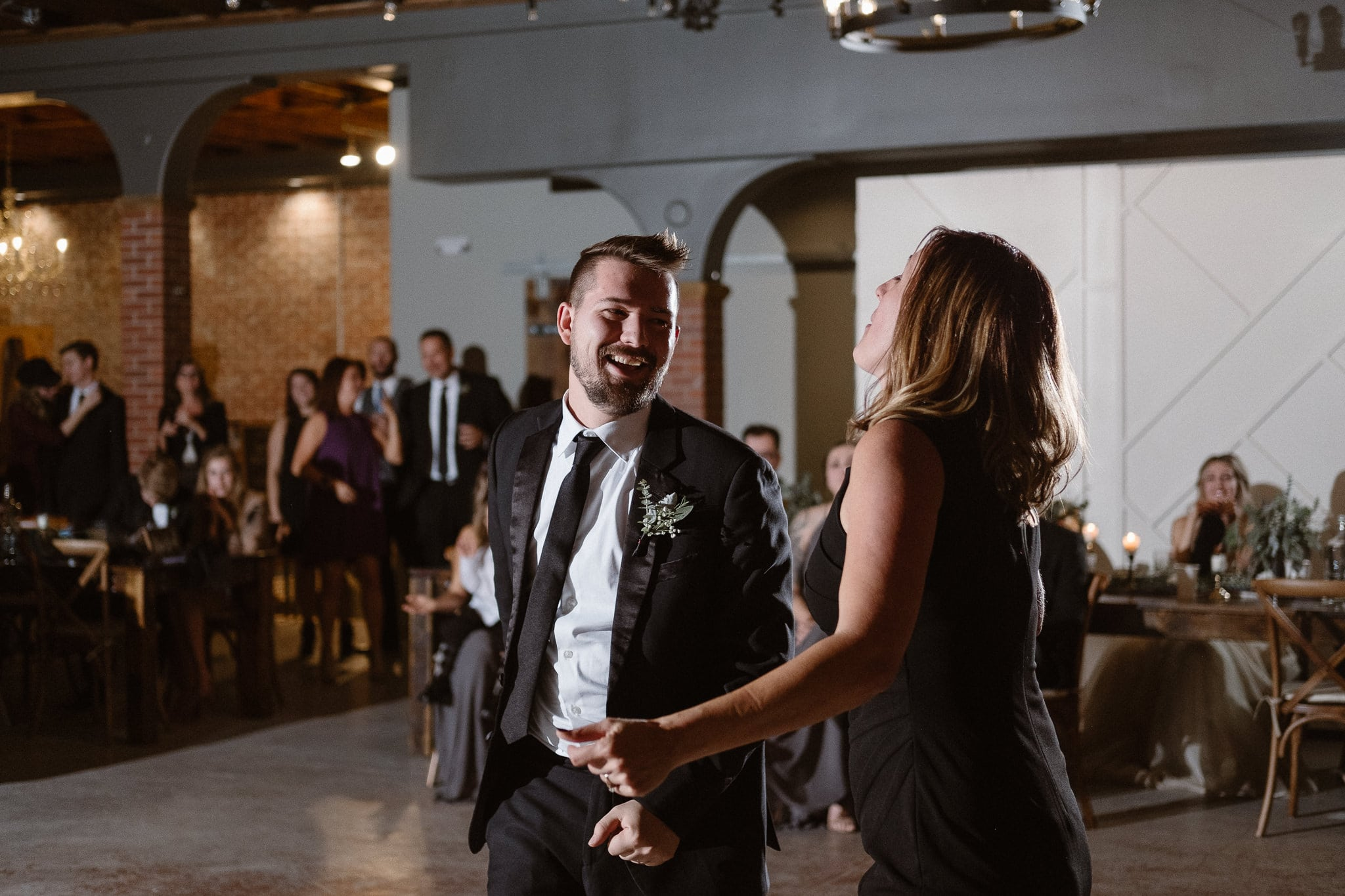 St Vrain Wedding Photographer | Longmont Wedding Photographer | Colorado Winter Wedding Photographer, Colorado industrial chic wedding ceremony, groom dancing with his mother, off camera flash photography reception lighting