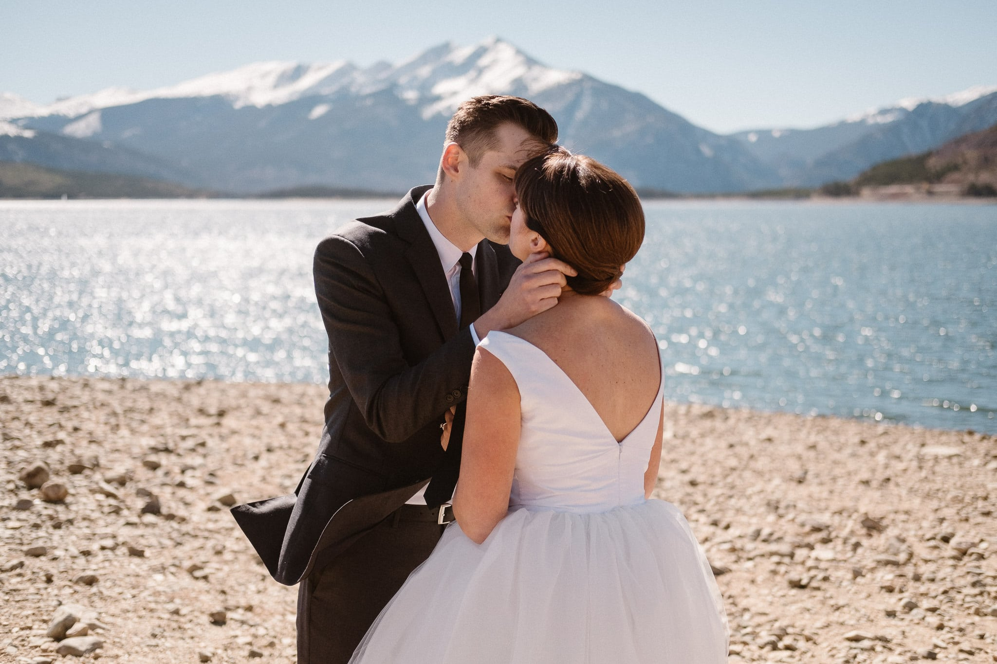Silverthorne Pavilion Wedding Photographer, Colorado mountain wedding photographer, bride and groom kissing by Lake Dillon with snowcapped mountains behind
