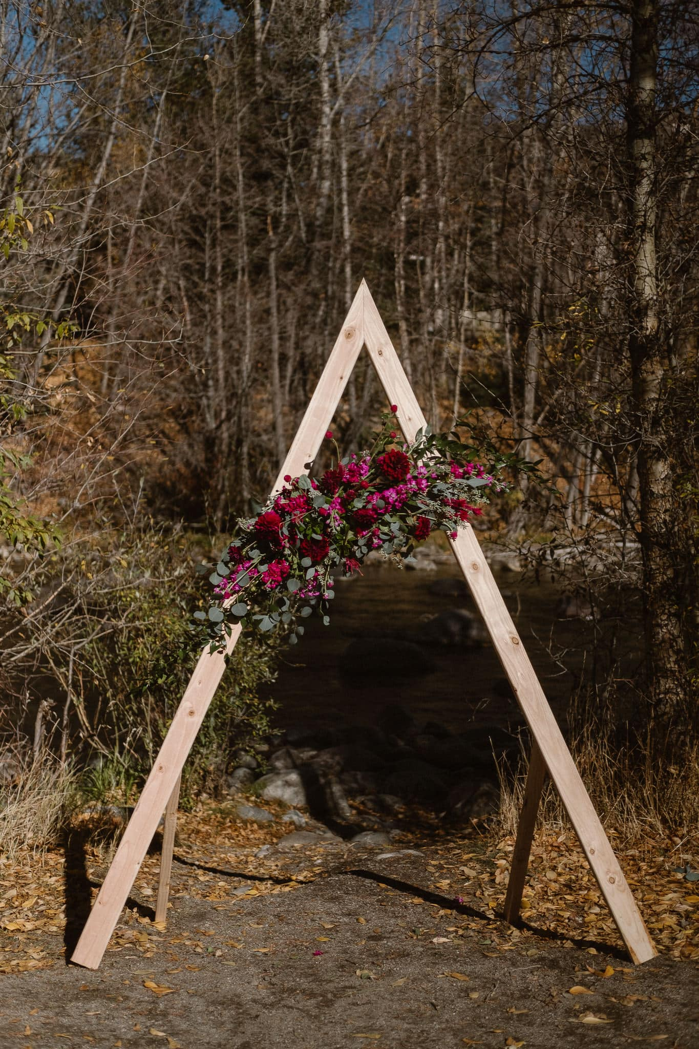 Silverthorne Pavilion wedding ceremony, triangle ceremony arch with flowers, Colorado wedding photographer, mountain wedding, winter wedding