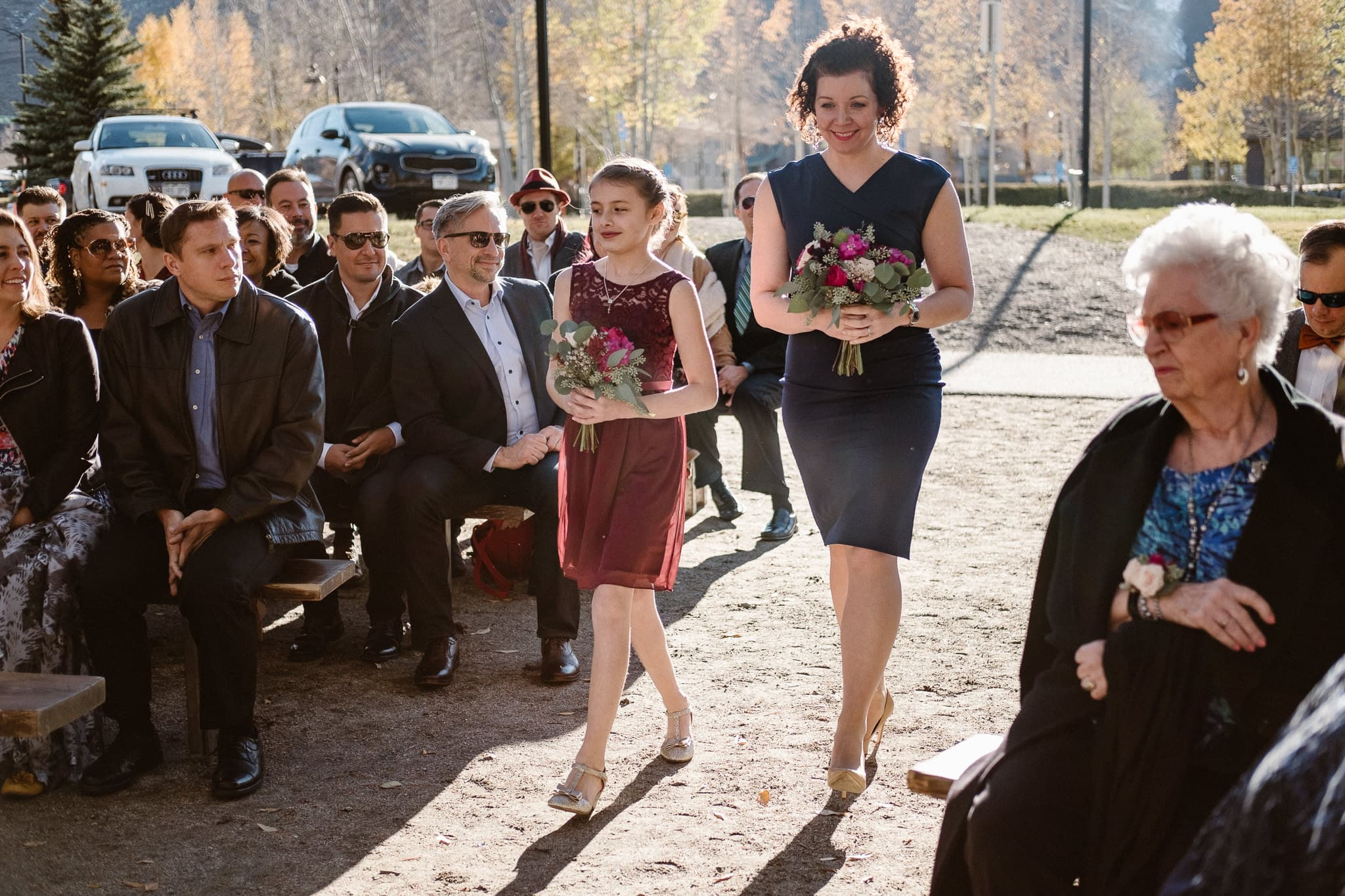 Silverthorne Pavilion wedding ceremony, Colorado wedding photographer, maid of honor and best woman walking down aisle