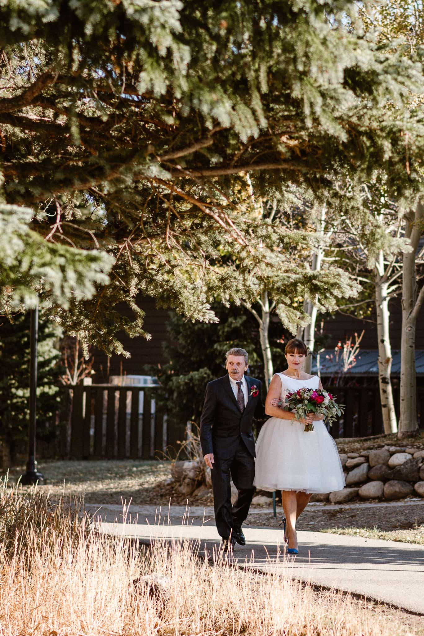 Silverthorne Pavilion wedding ceremony, Colorado wedding photographer, bride and her father walking down the aisle