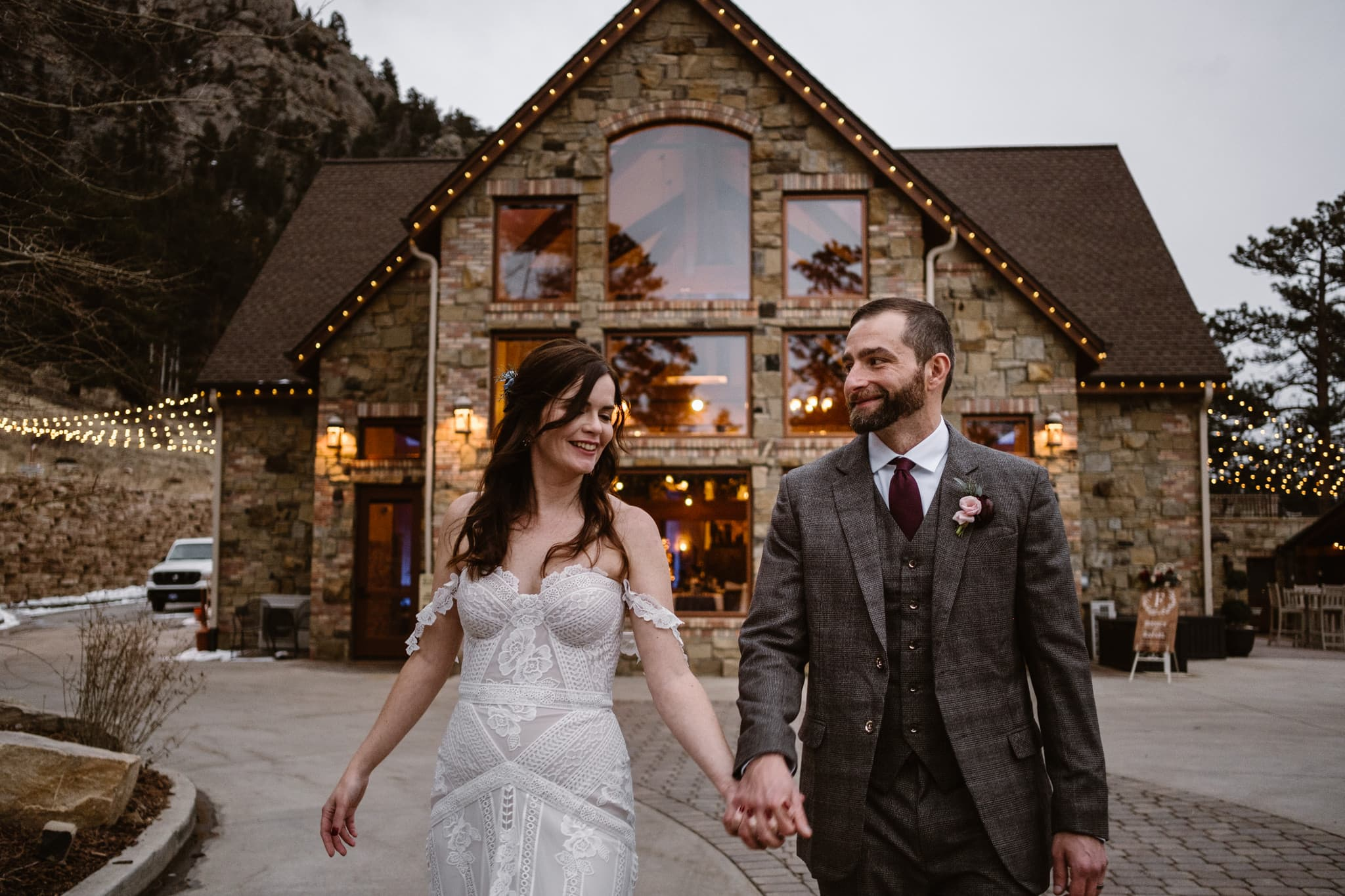 Della Terra Mountain Chateau winter wedding, Estes Park wedding photographer, bride and groom walking in front of wedding venue at dusk