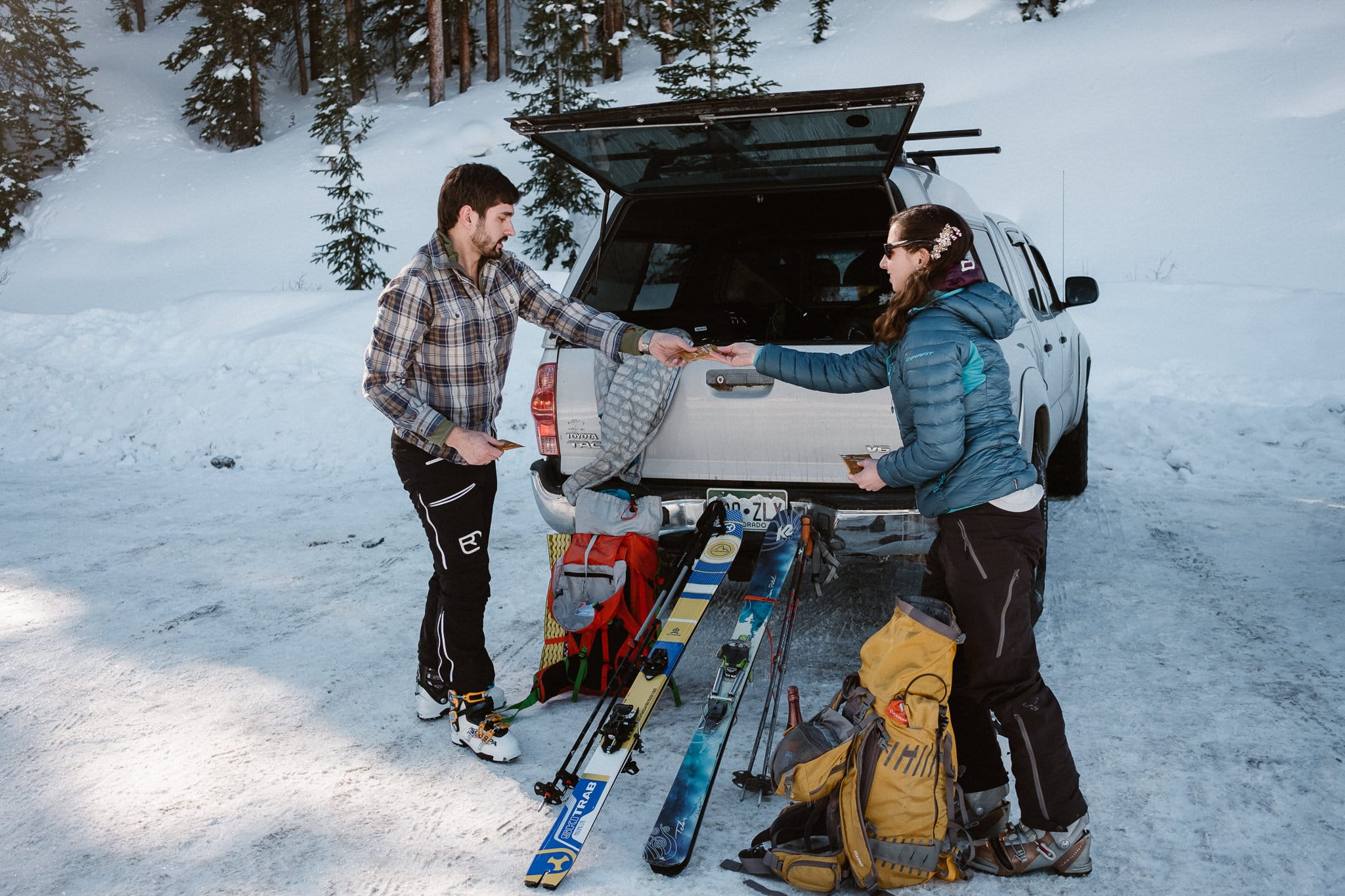 Bride and groom getting backcountry skis out of their car