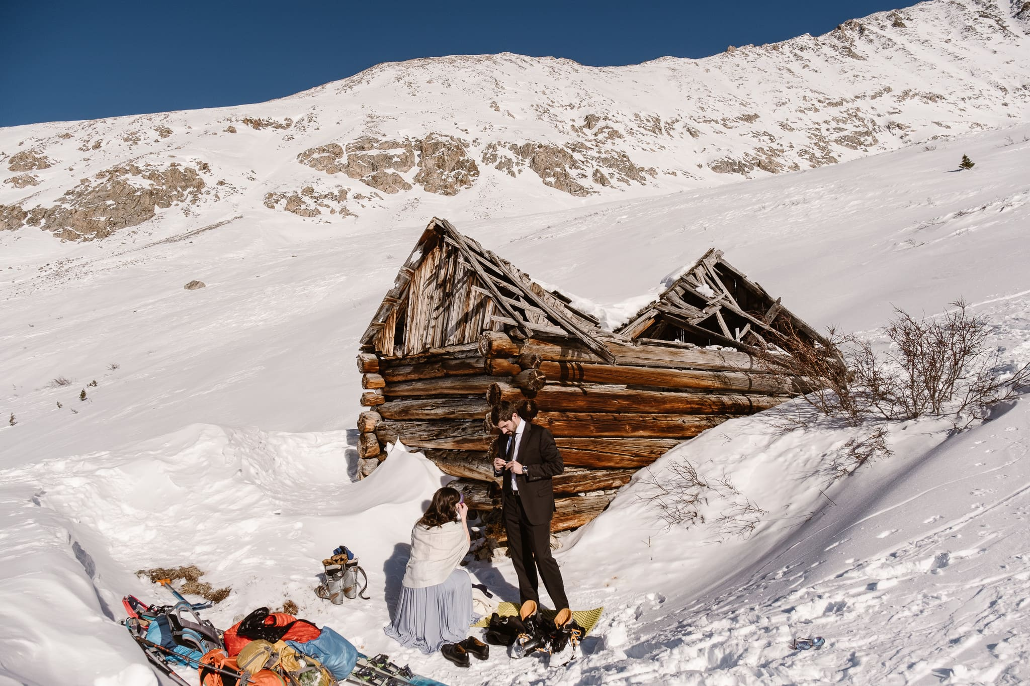 Bride and groom getting dressed by old mining cabin, Colorado winter elopement in the mountains, backcountry skiing elopement