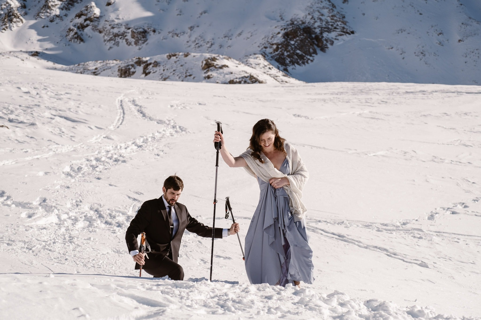 Bride and groom hiking with ski poles in snow, winter backcountry skiing elopement in Colorado mountains, adventure elopement photography
