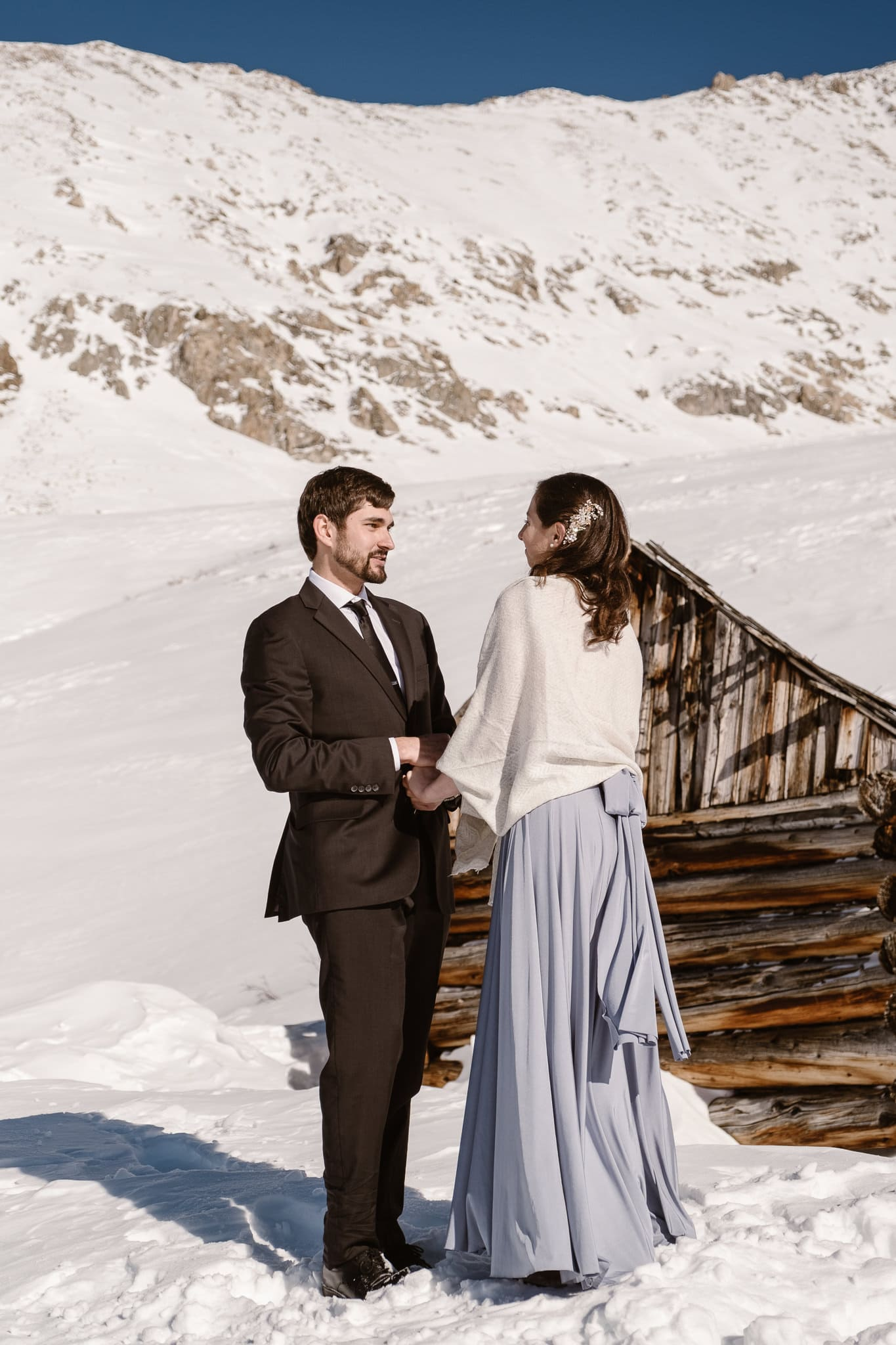 Bride and groom exchanging vows in snow covered mountains of Colorado, winter elopement photography