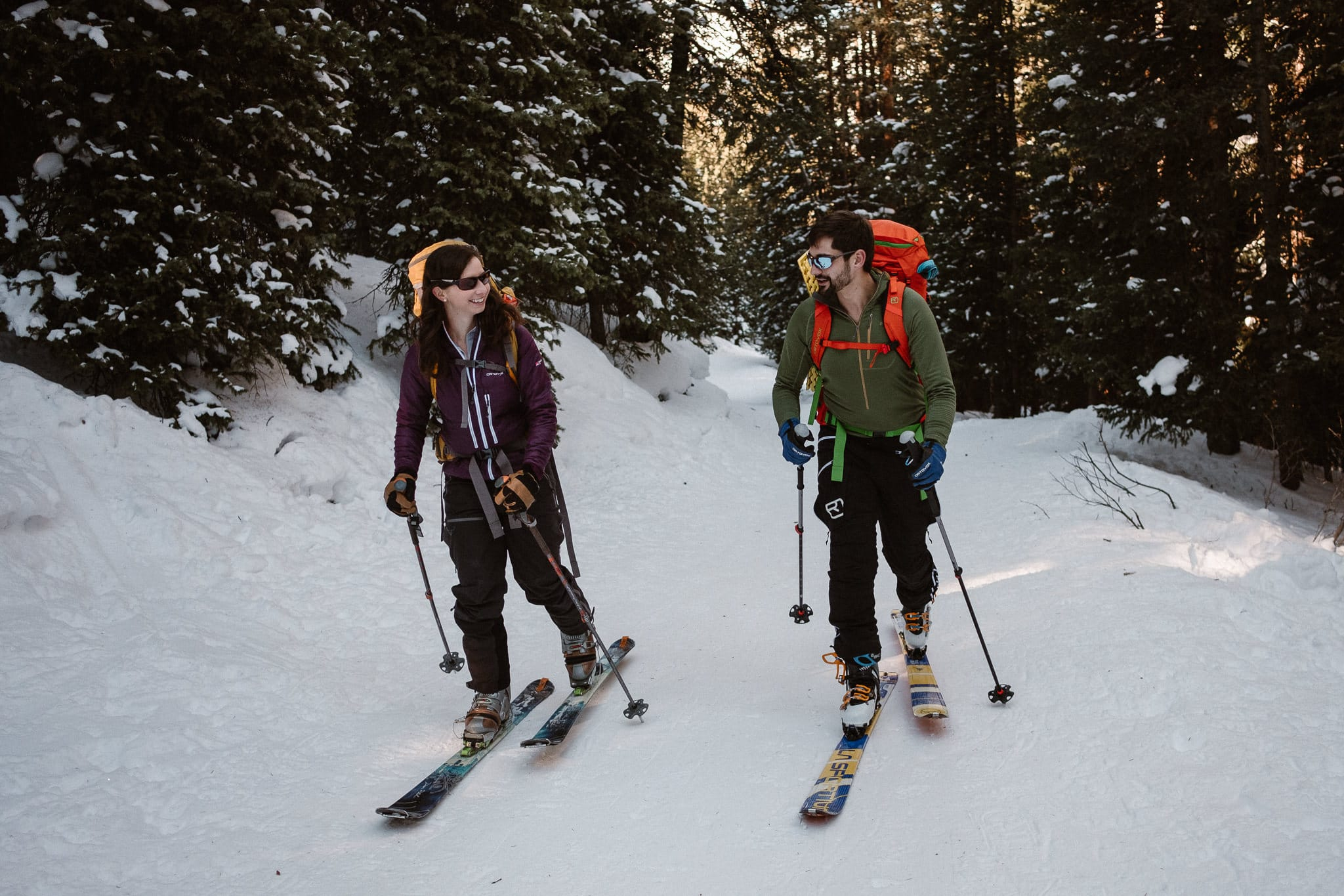 Bride and groom skinning up snow-covered trail, backcountry skiing elopement in Colorado