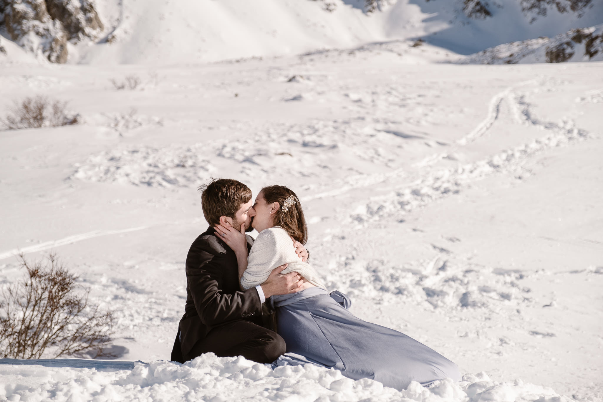 Bride and groom falling over in snow during first kiss, winter mountain elopement, Colorado snow elopement, winter wedding