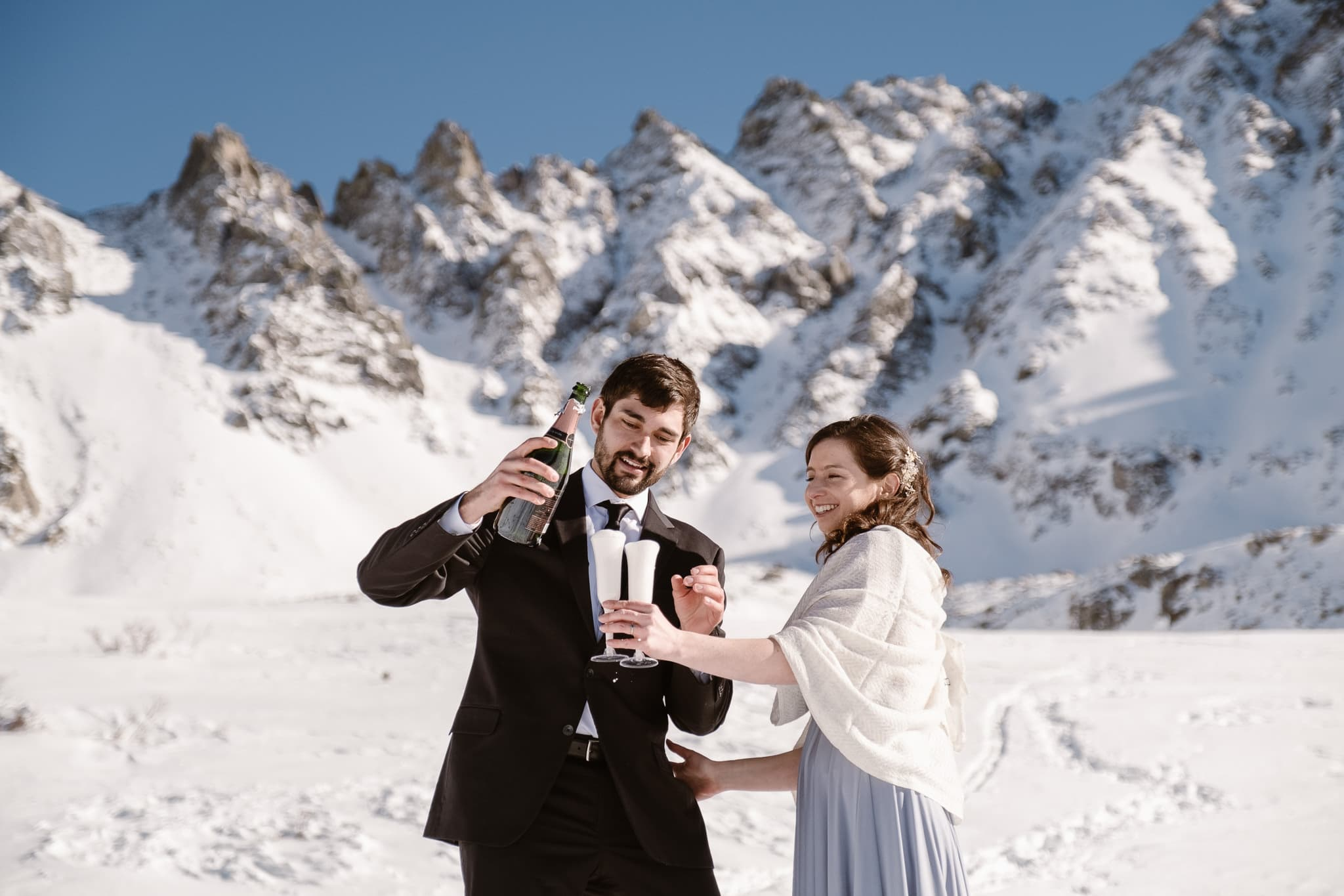 Bride and groom popping champagne bottle, winter mountain elopement, Colorado ski wedding, backcountry skiing elopement