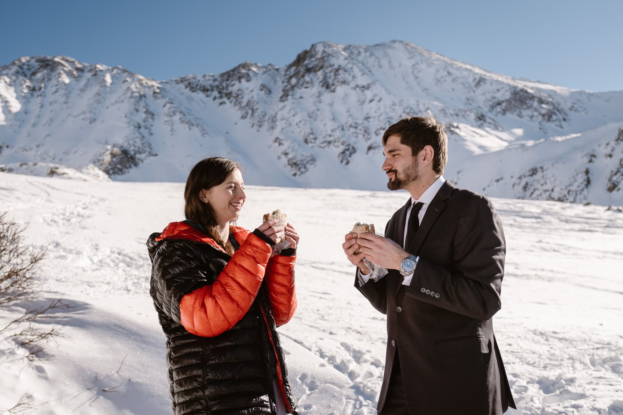Bride and groom eating PB&J sandwiches after their wedding ceremony, winter mountain elopement, Colorado adventure photographer
