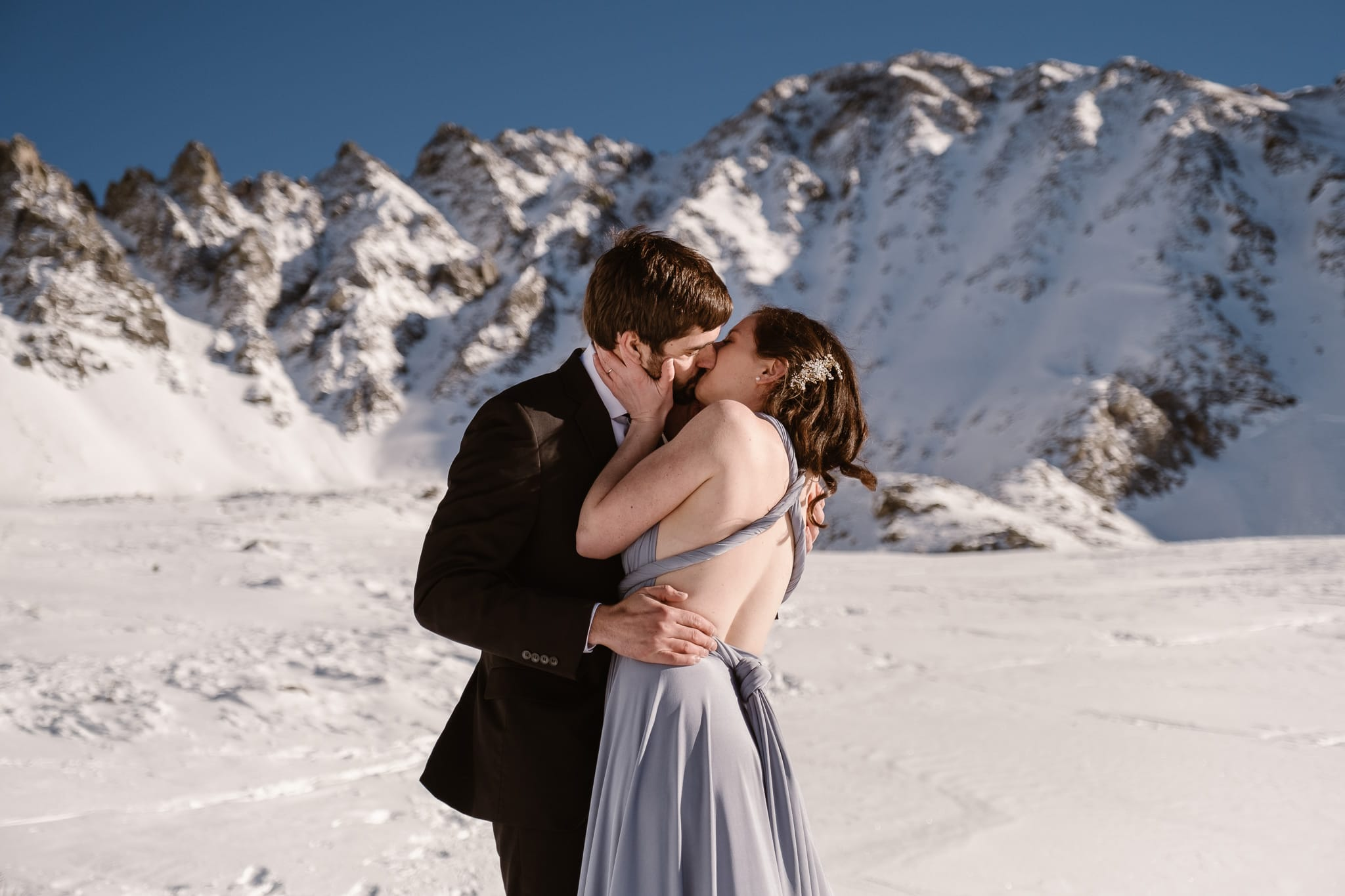 Backcountry skiing elopement, Colorado adventure wedding photographer, bride and groom kissing in snow covered mountains, best month to elope in Colorado, January elopement