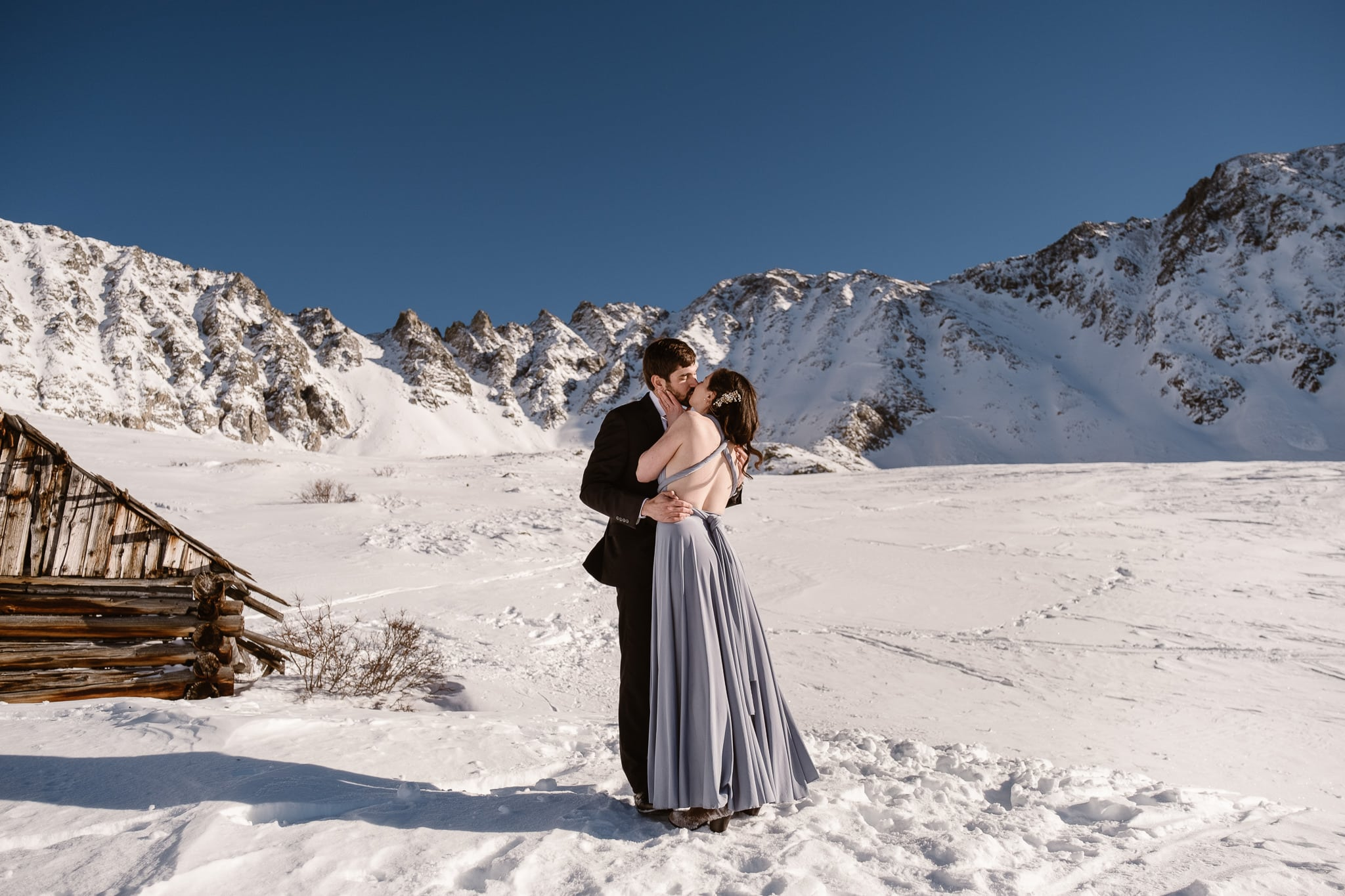 Backcountry skiing elopement in the snow-covered mountains of Colorado, bride wearing light blue wedding dress with open back