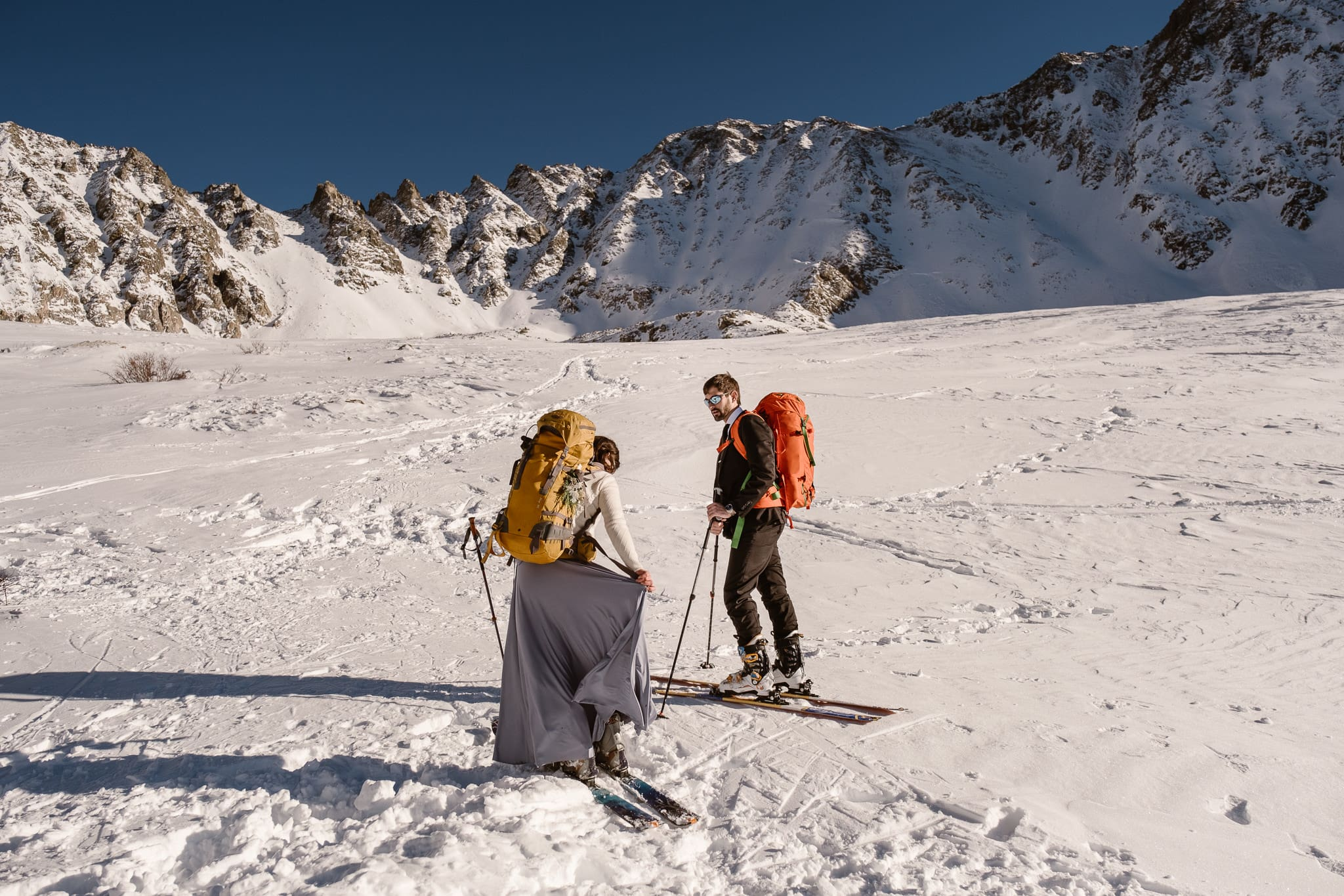 Bride and groom backcountry skiing in the Colorado mountains, Leadville elopement, bride skiing in wedding dress