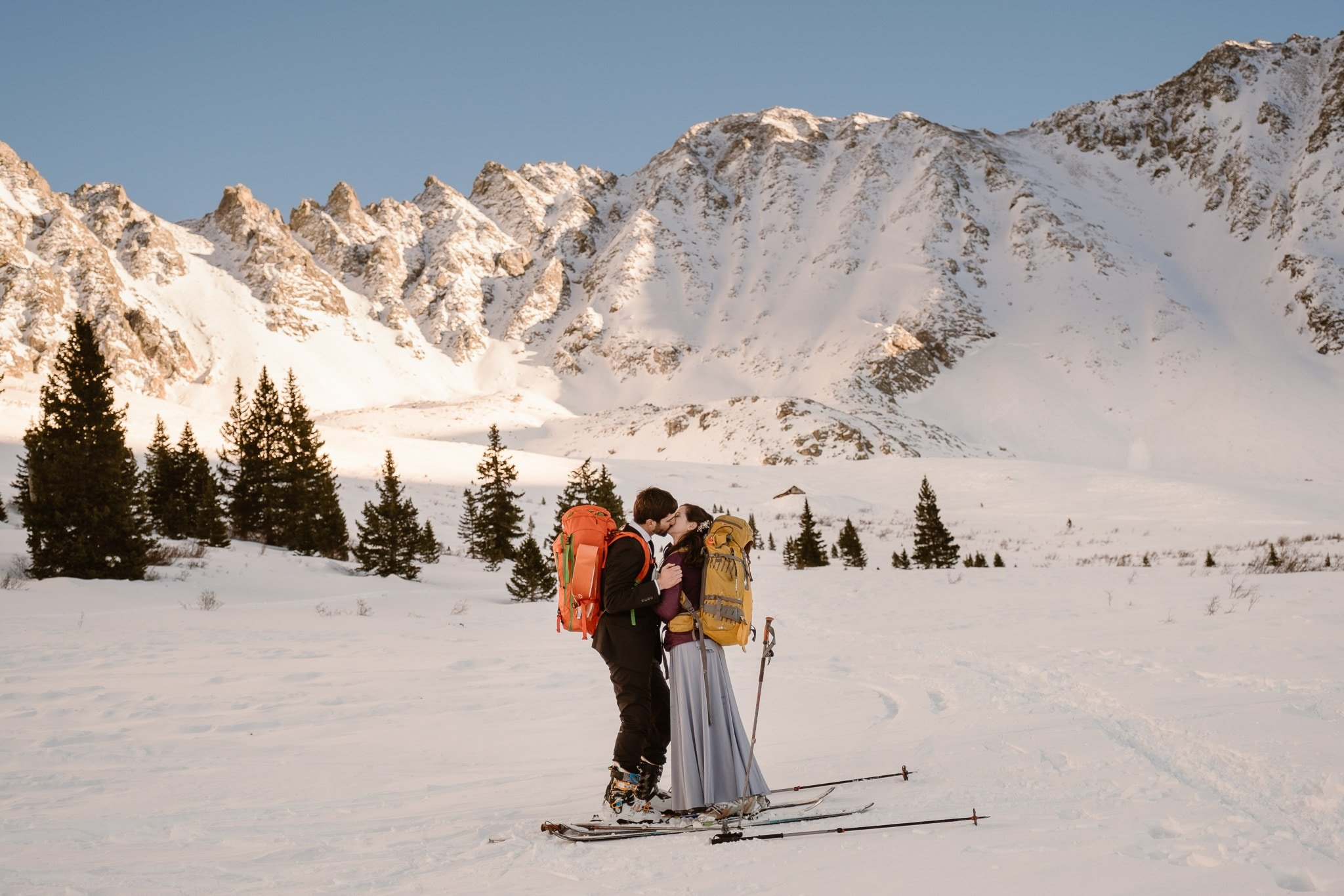 Bride and groom wearing backpacks, winter skiing elopement in Colorado mountains, backcountry skiing wedding